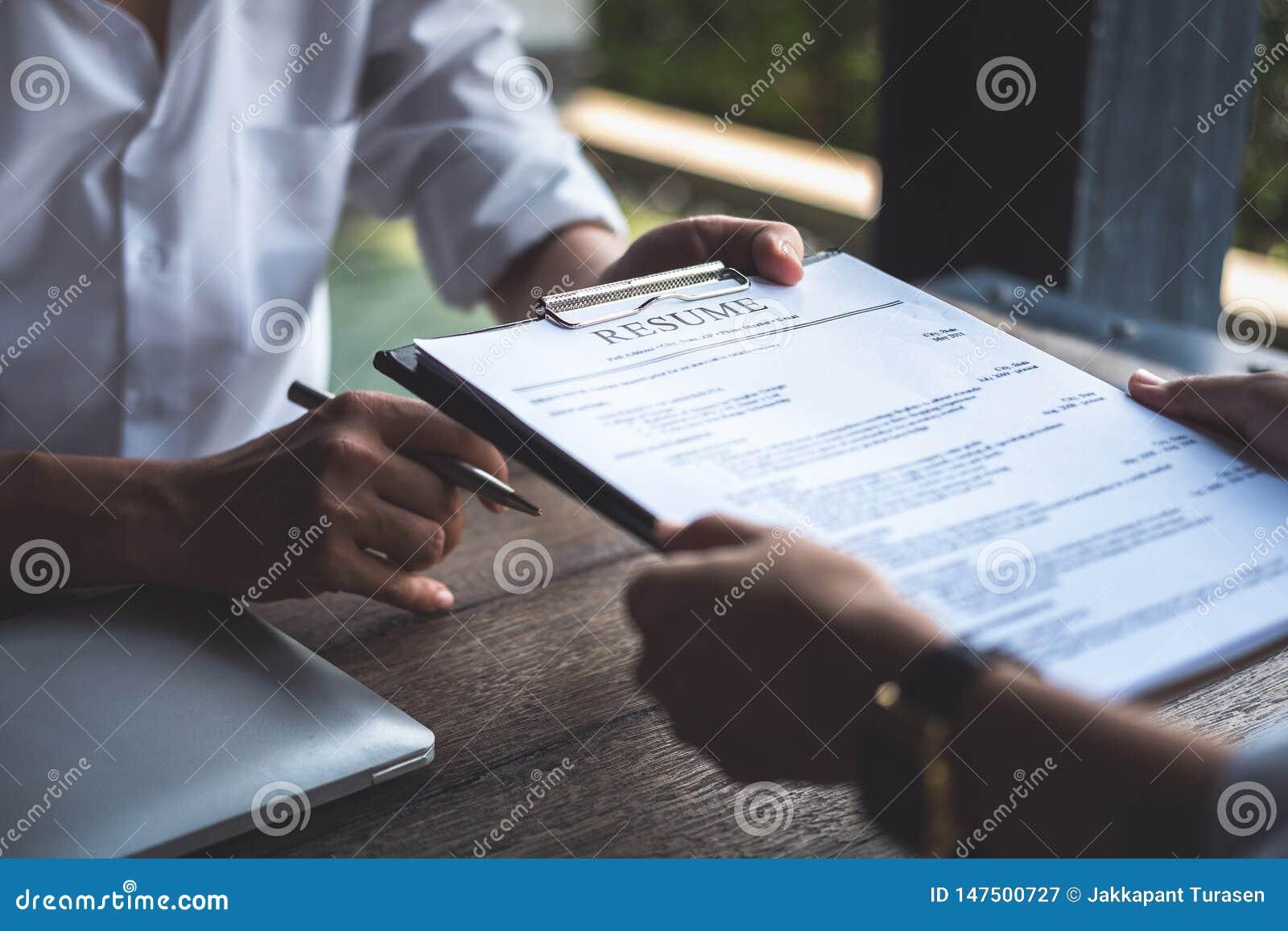 La mujer presenta la solicitud de trabajo, entrevistador que lee un curriculum vitae