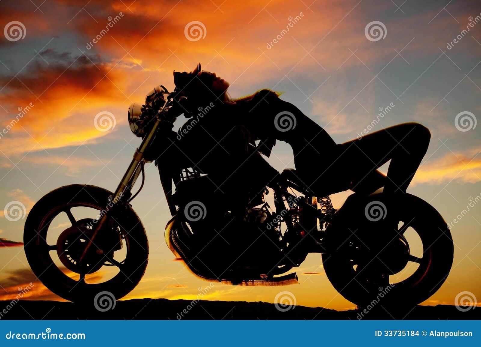 La mujer puesta encendido apoya de silueta de la motocicleta