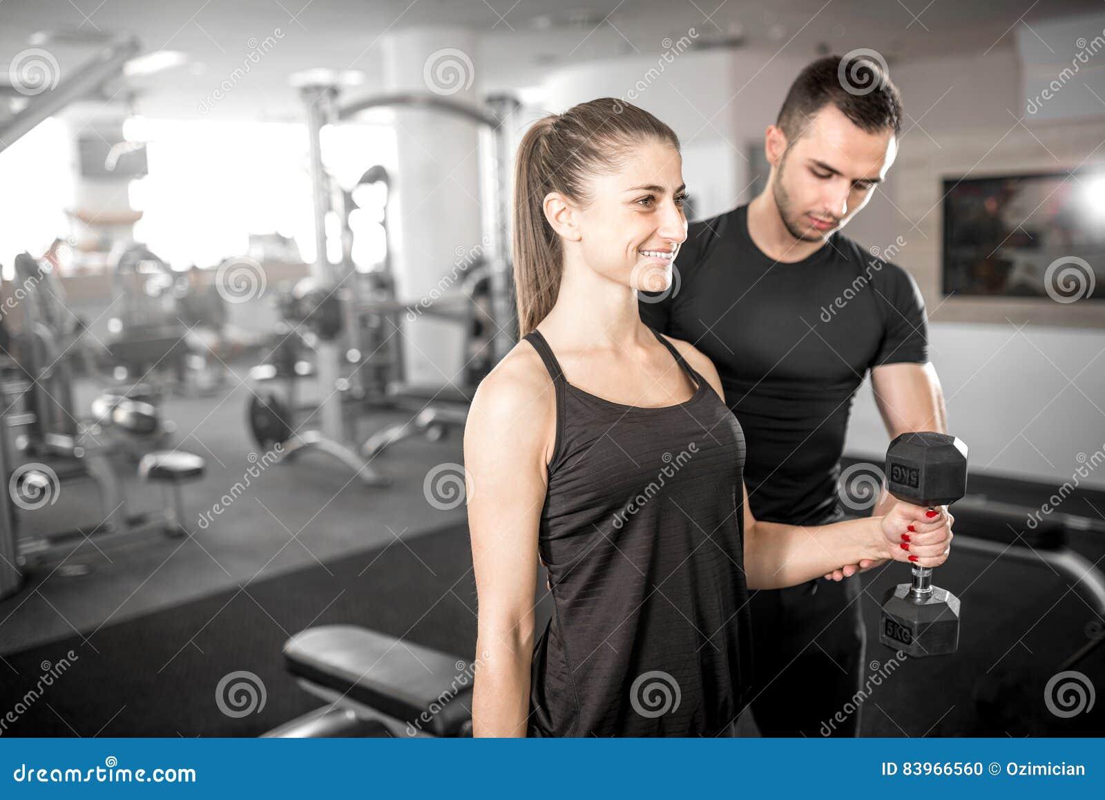 La mujer que hace el bíceps se encrespa en gimnasio con su instructor personal