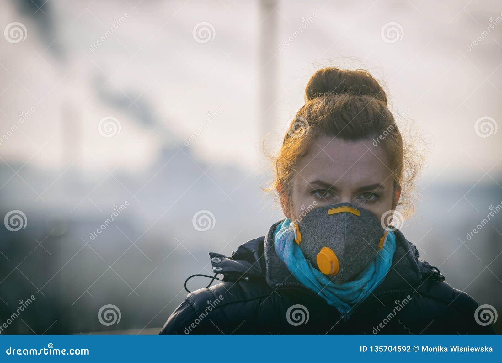 La mujer que lleva un anticontaminación real, contra la niebla y los virus la mascarilla