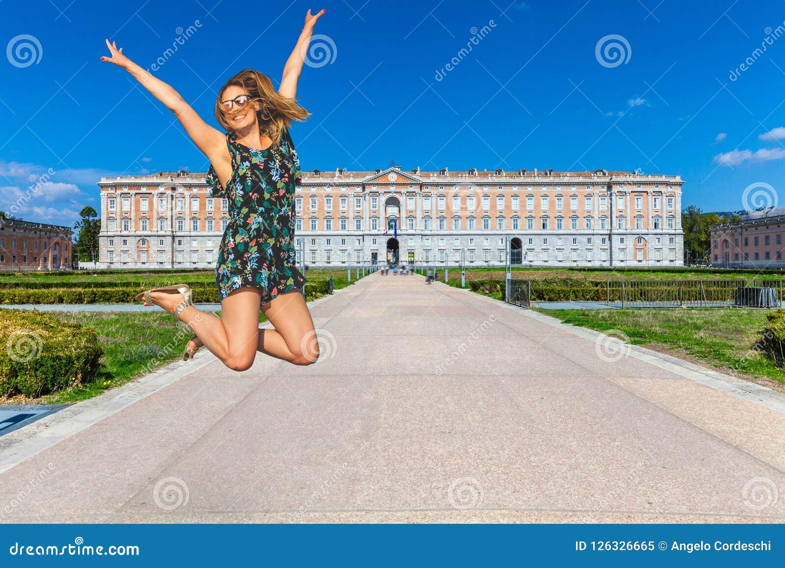 La mujer que salta con felicidad con los brazos para arriba Palacio real de Caserta en Italia Recorrido en Italia