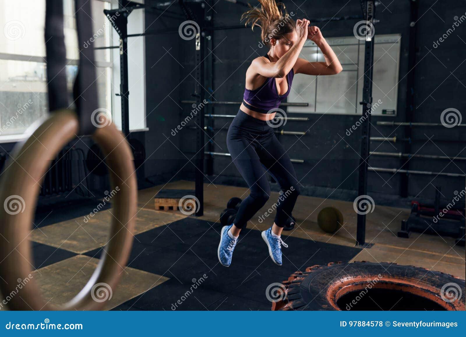 La mujer que salta en el neumático enorme en el gimnasio de CrossFit