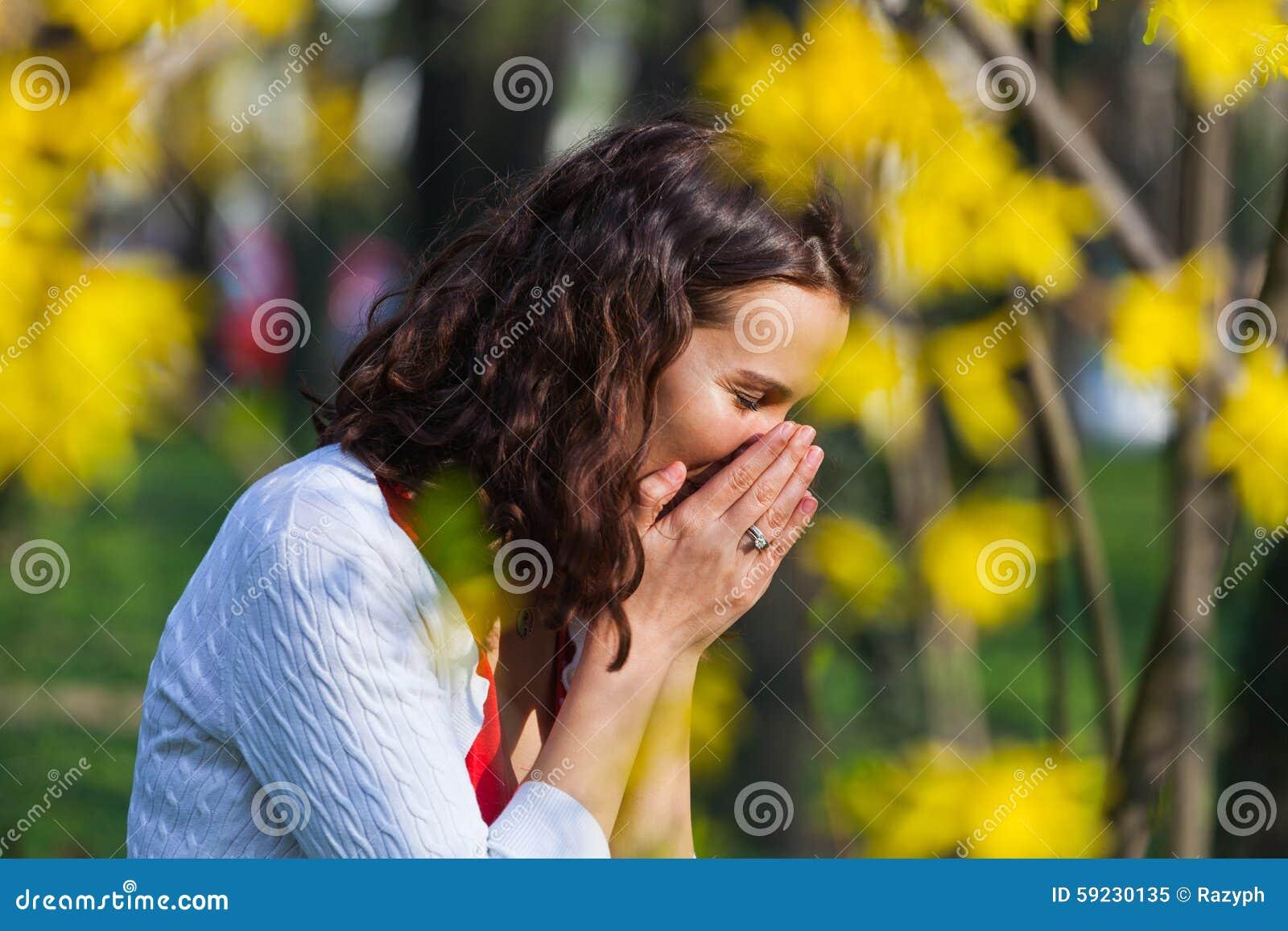 Download La Mujer Que Se Coloca Cerca De Las Flores Está Estornudando Imagen de archivo - Imagen de cerrado, brunette: 59230135