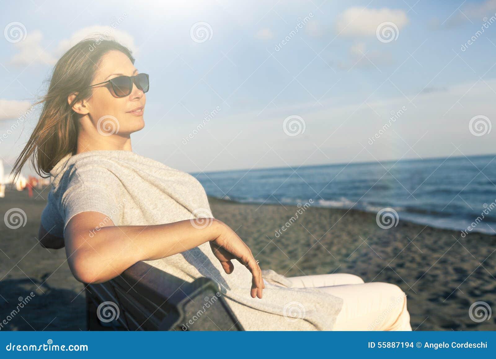 La mujer que se relajaba en el mar se vistió en la paz que se sentaba en el banco en la playa Gafas de sol