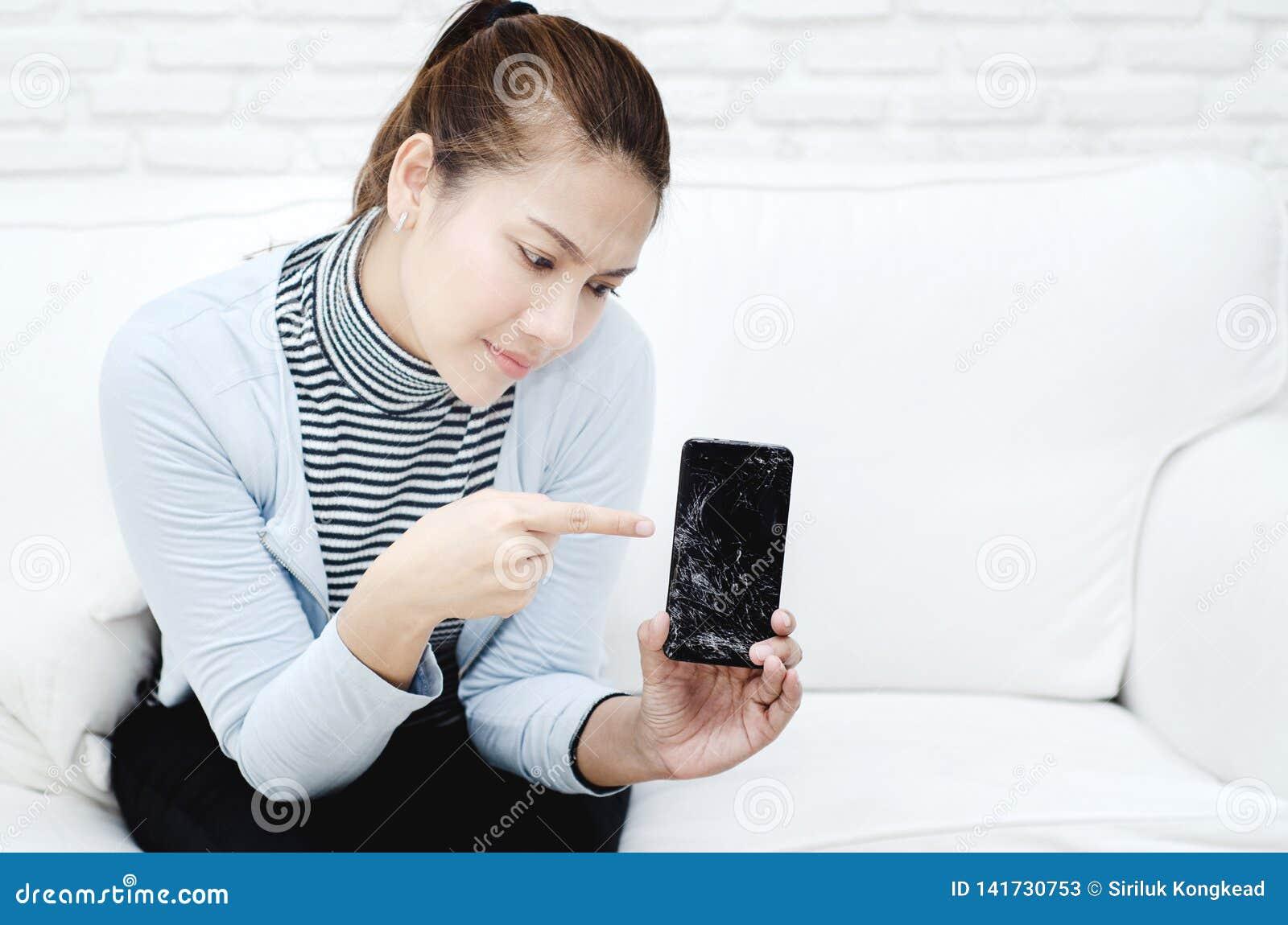 La mujer que se sienta en el sofá que lleva una camisa azul el teléfono móvil está quebrada en la mano