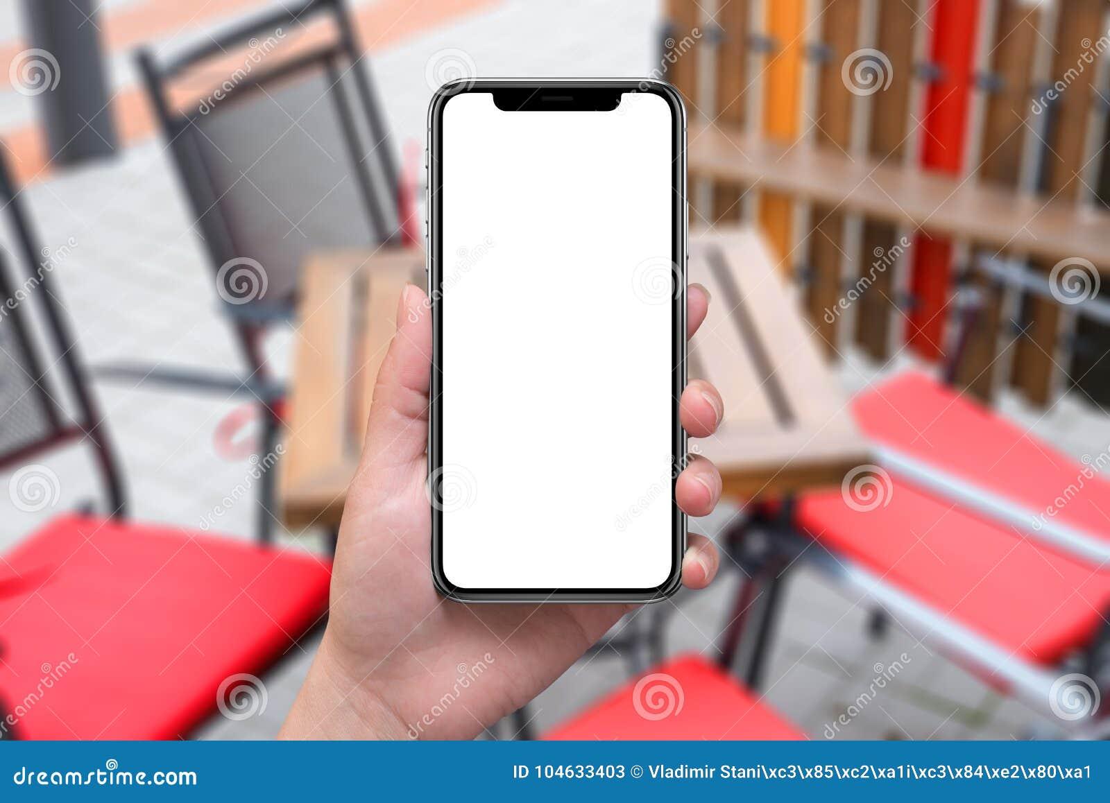 La mujer que sostenía el teléfono elegante negro moderno con x curvó los bordes