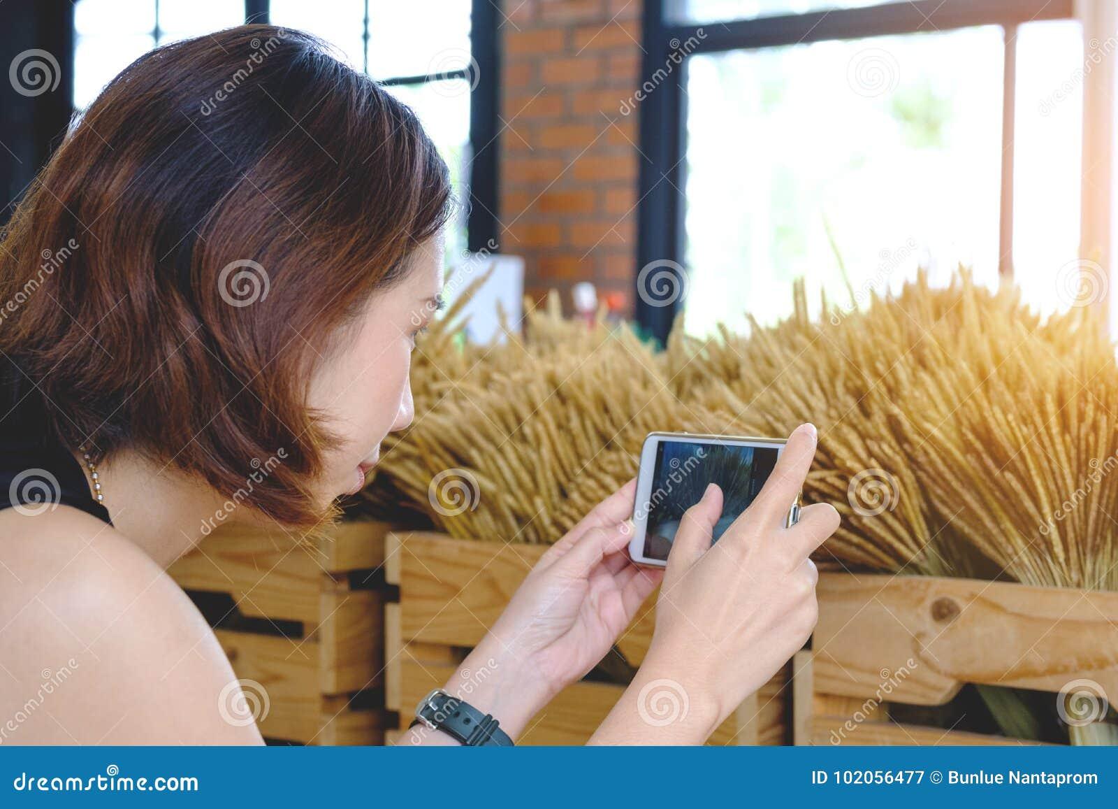 La mujer que toma la foto con el teléfono móvil, muchacha tailandesa joven toma la foto