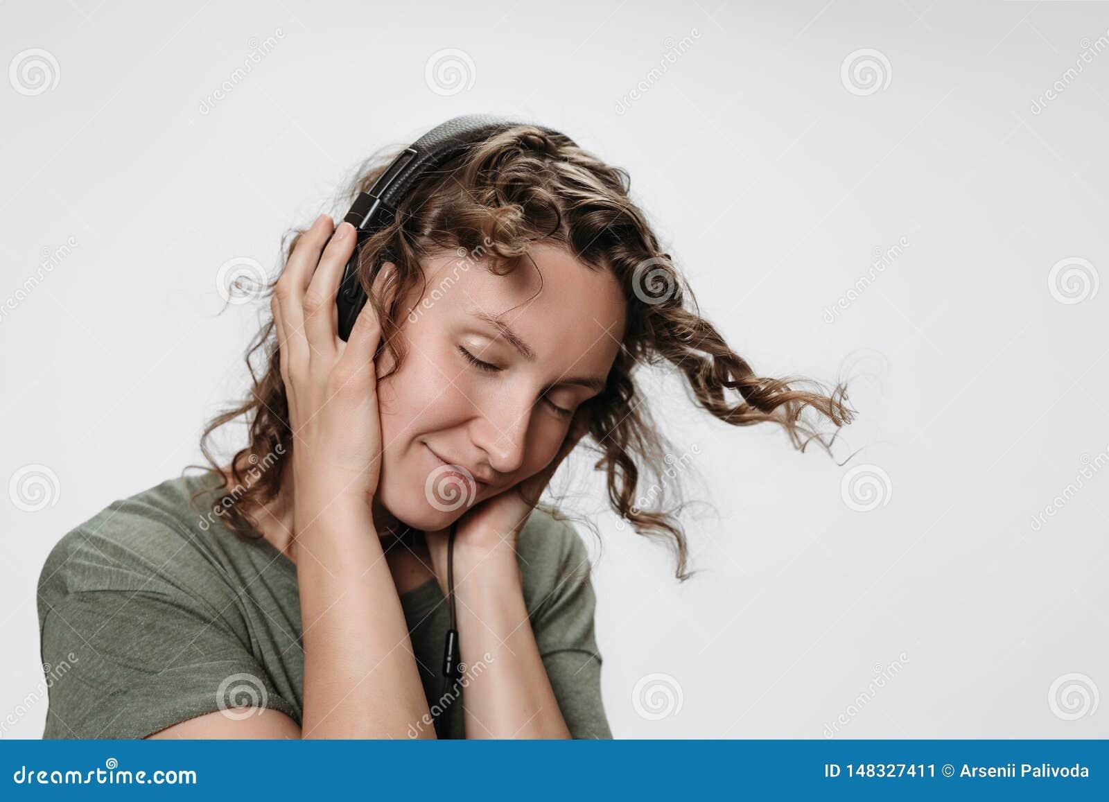 La mujer rizada joven alegre despreocupada escucha m?sica preferida con la mano en sus auriculares