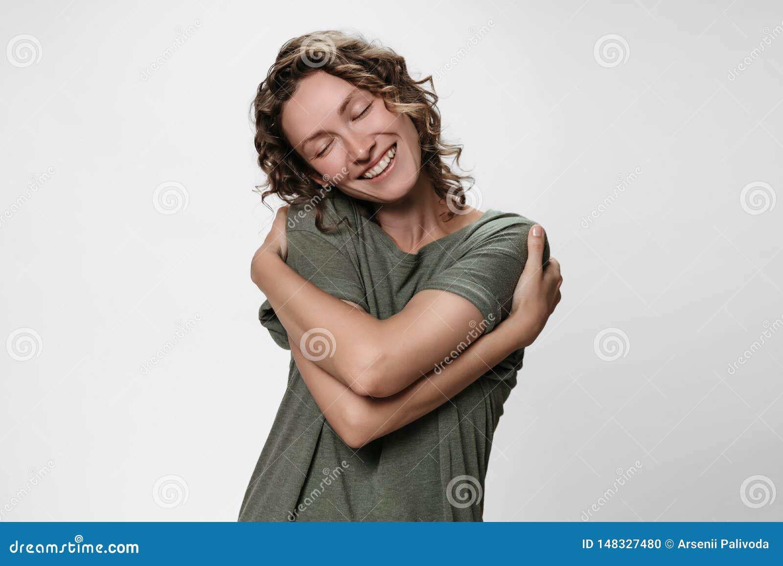La mujer rizada joven que se abraza, parece feliz, expresa emociones positivas naturales