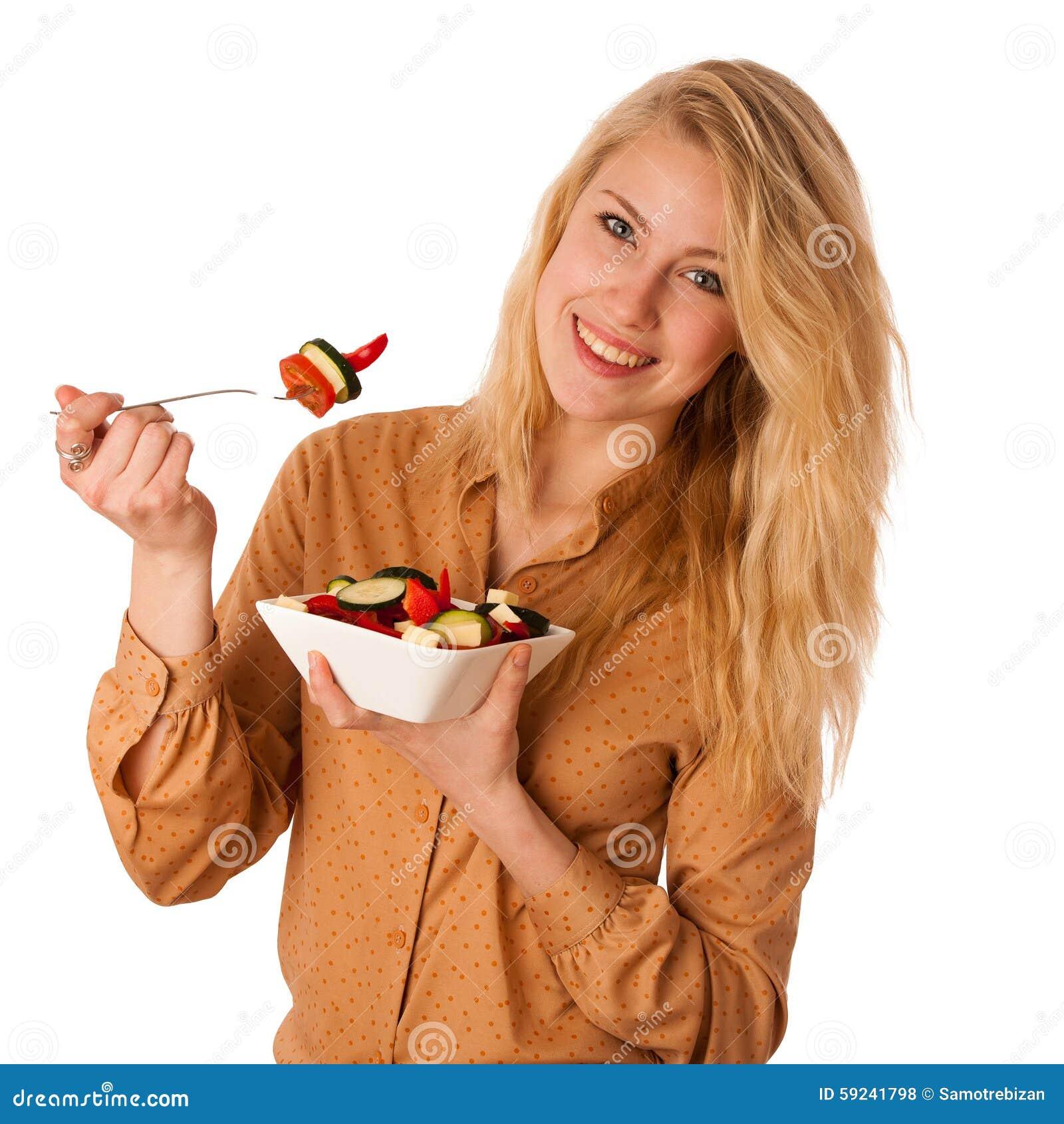 La mujer rubia caucásica joven hermosa come una ensalada deliciosa a