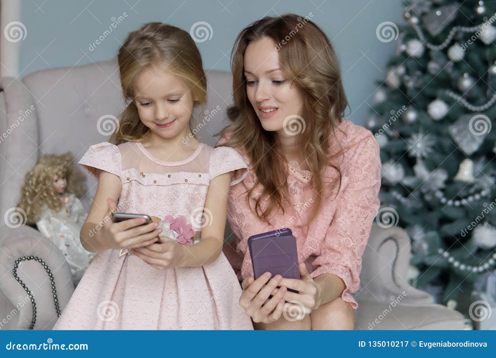 La mujer rubia en una blusa rosada se sienta en el sofá y sostiene un teléfono móvil en una caja púrpura al lado de hija las mira
