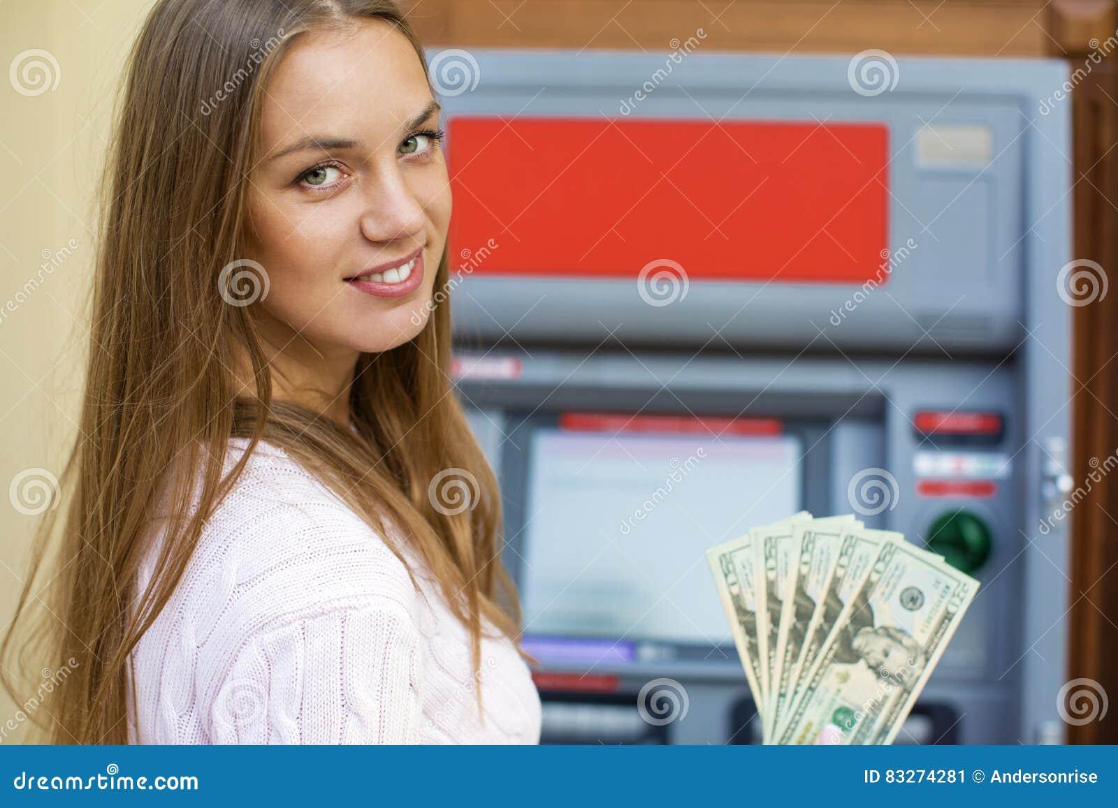 La mujer rubia joven está llevando a cabo dólares de un efectivo
