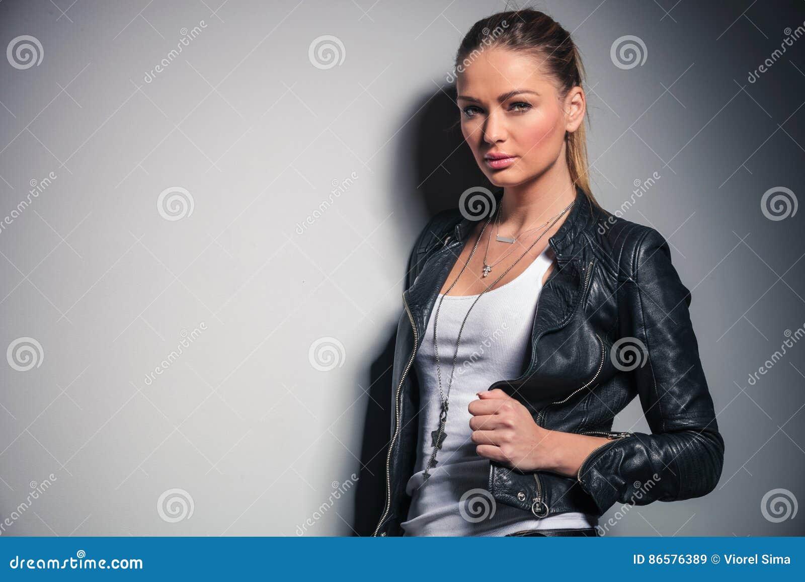 La mujer rubia linda en la chaqueta de cuero sostiene su cuello