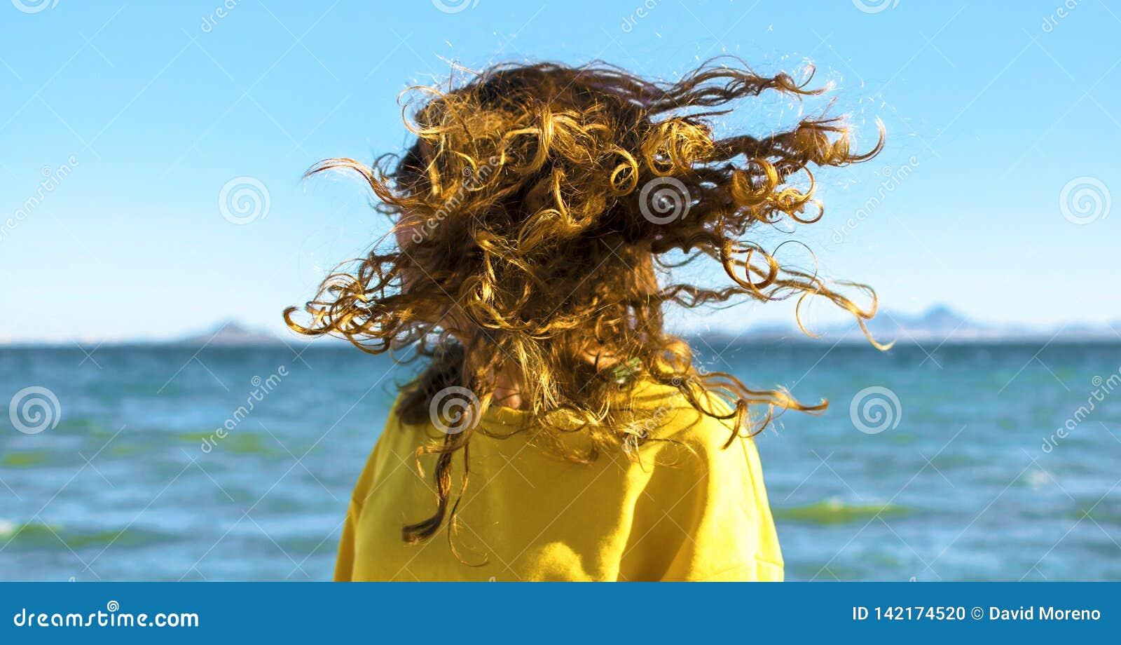 La mujer rubia sacude la cabeza con el pelo rizado en la playa