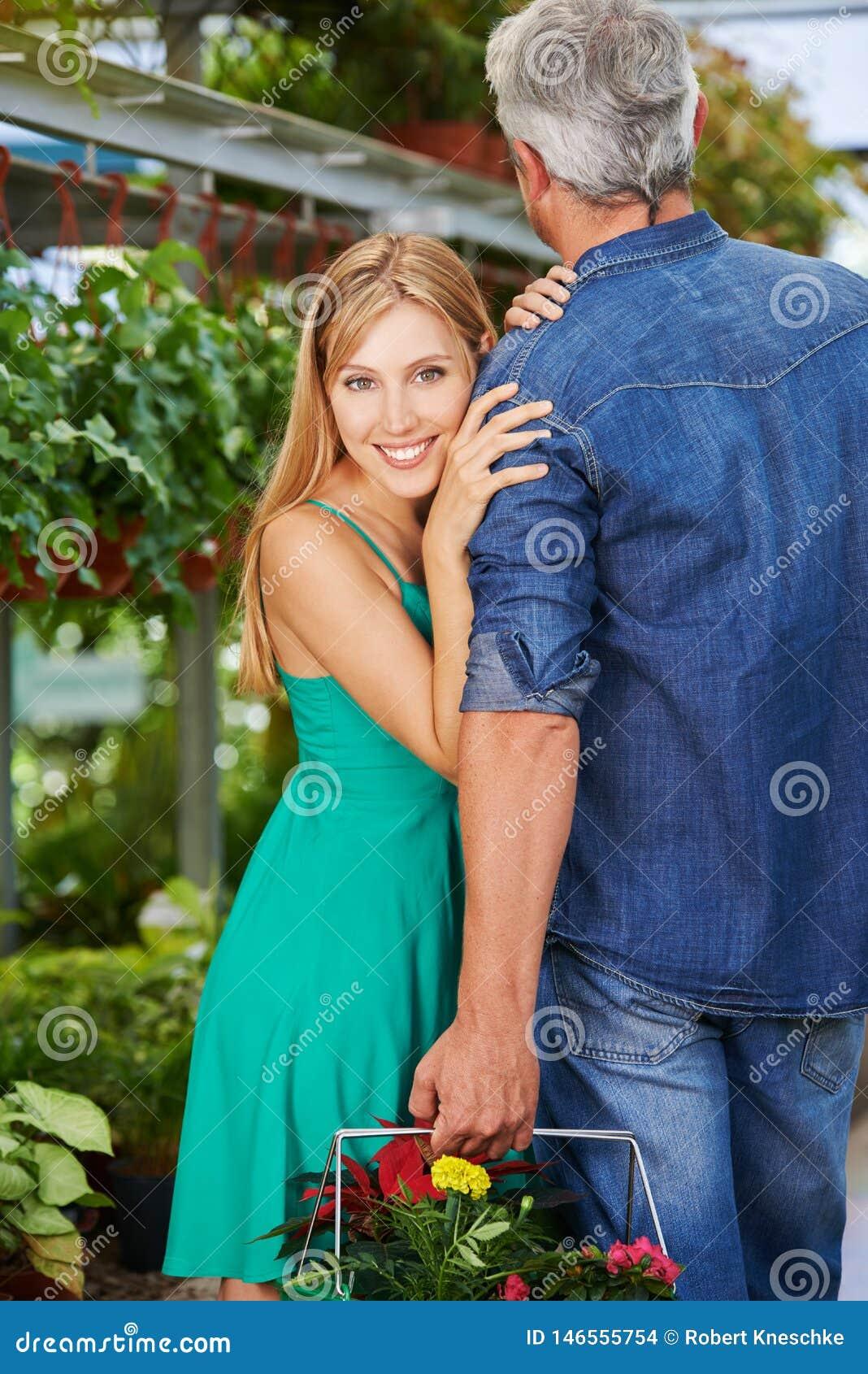 La mujer se está inclinando contra el hombro del hombre en centro de jardinería