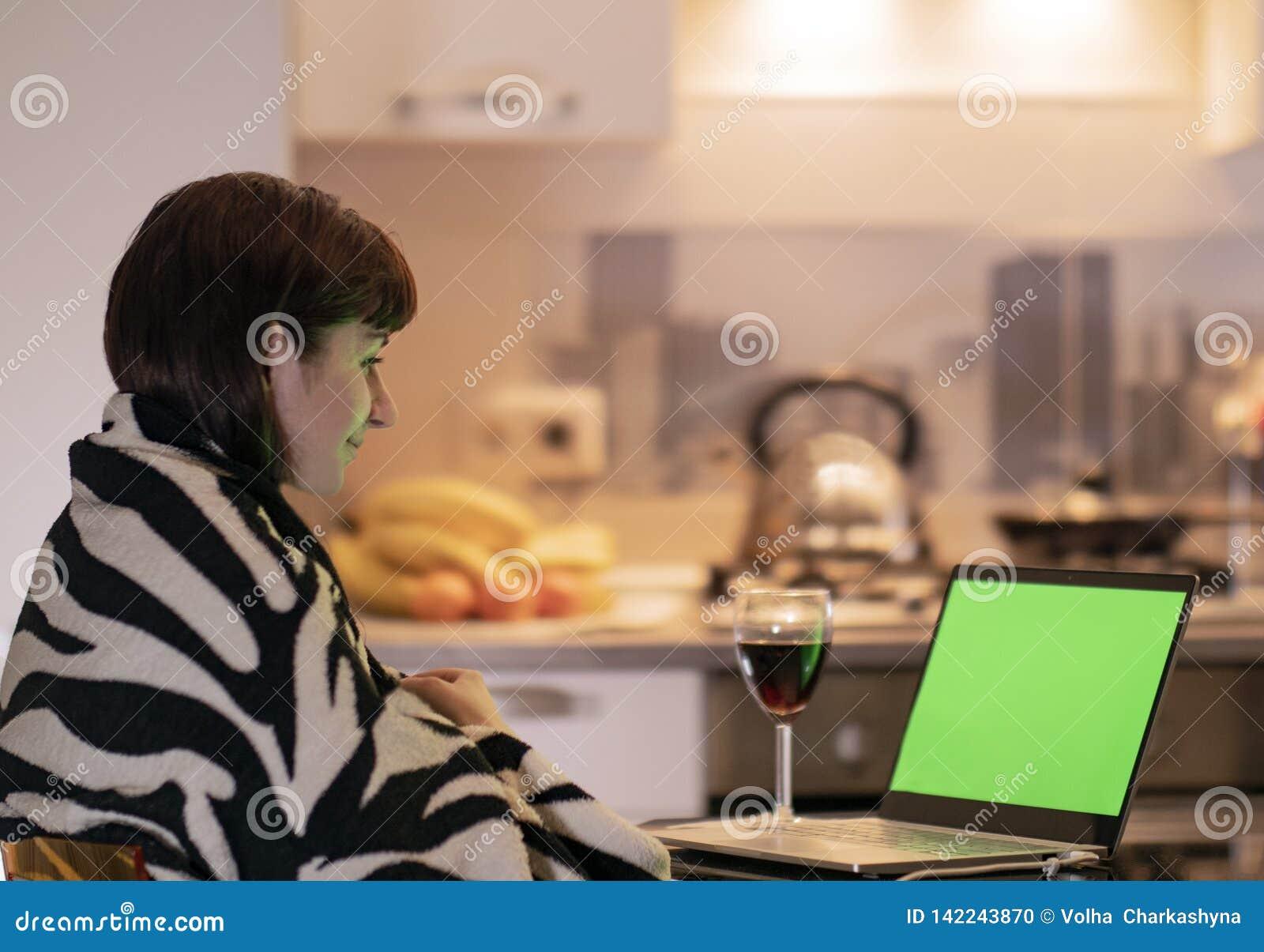La mujer se está sentando en la cocina en la tabla por el ordenador portátil y con una sonrisa mira la pantalla de monitor, chrom