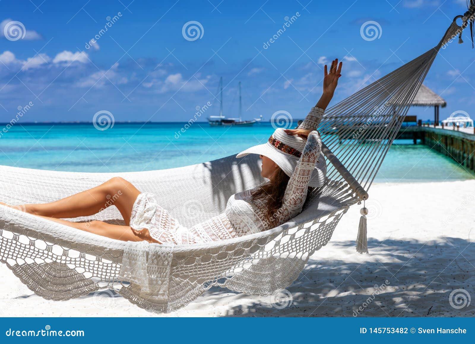La mujer se relaja en una hamaca en una playa tropical