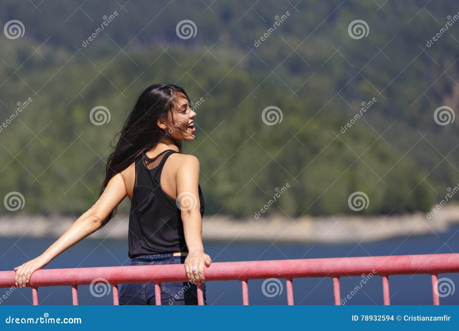 La mujer se sienta al borde de una presa