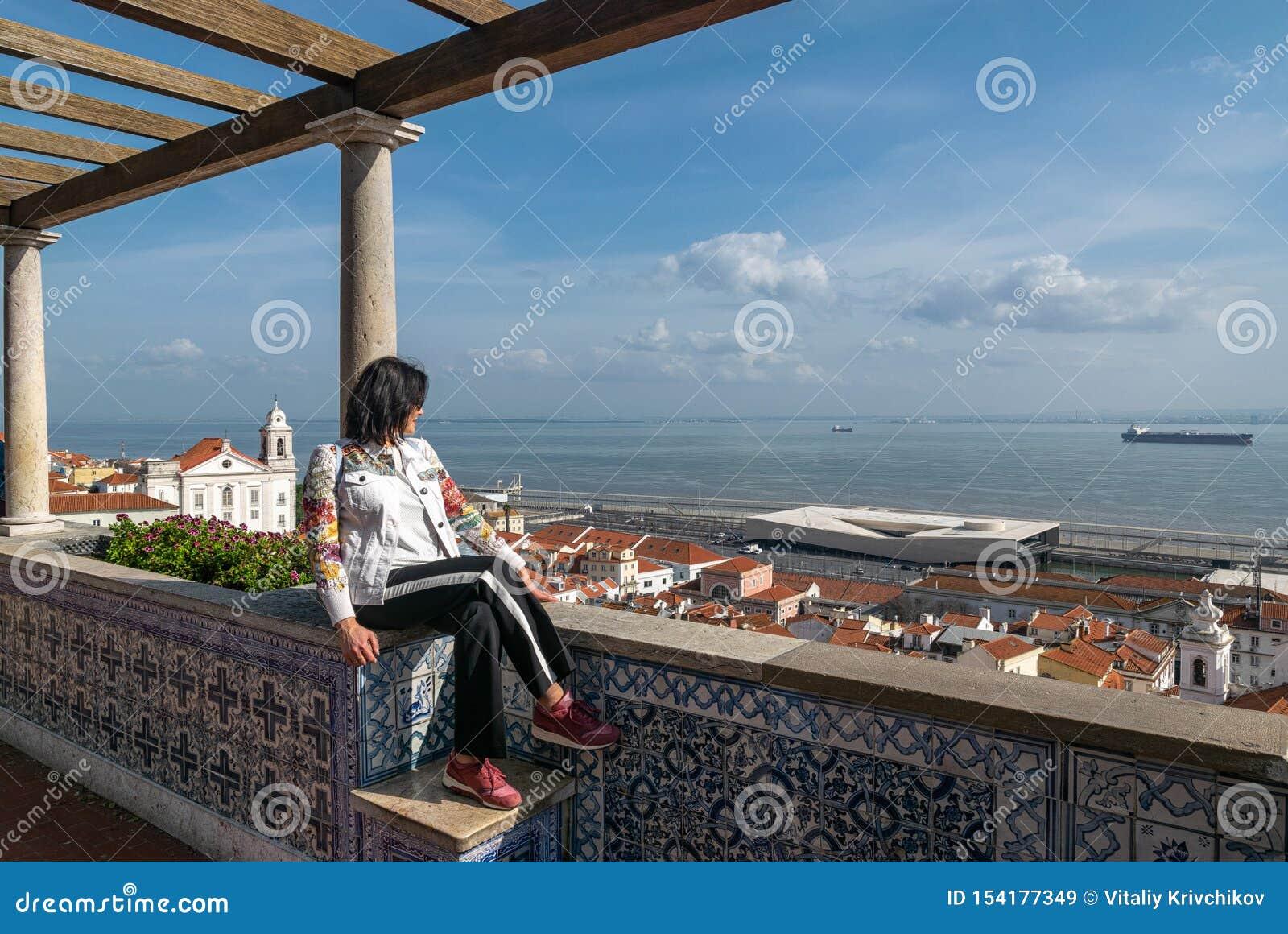 La mujer se sienta en la plataforma de observación y las miradas en los tejados de la ciudad, el mar, la nave, el cielo con las n