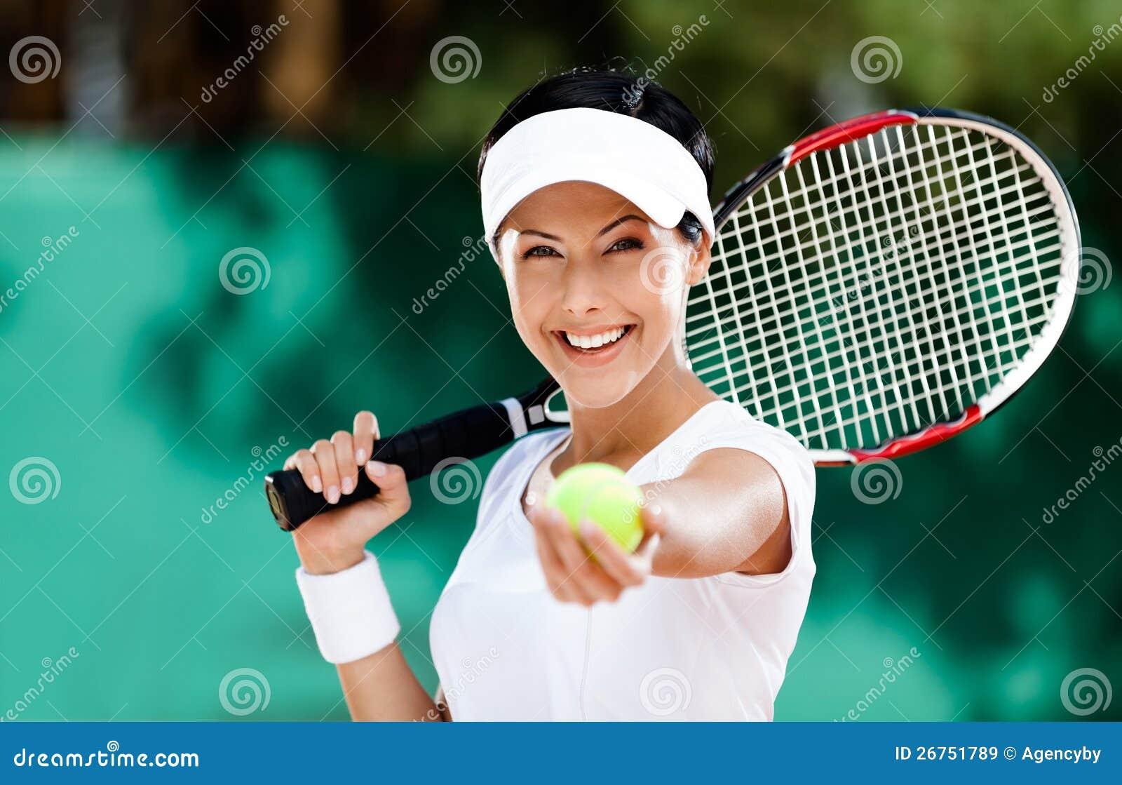 La mujer sirve la pelota de tenis