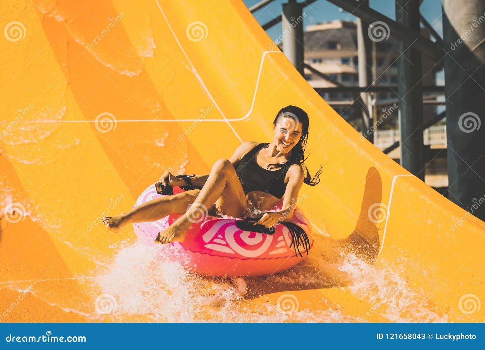 La mujer sonriente que se divierte en el tobogán acuático en aguamarina parquea
