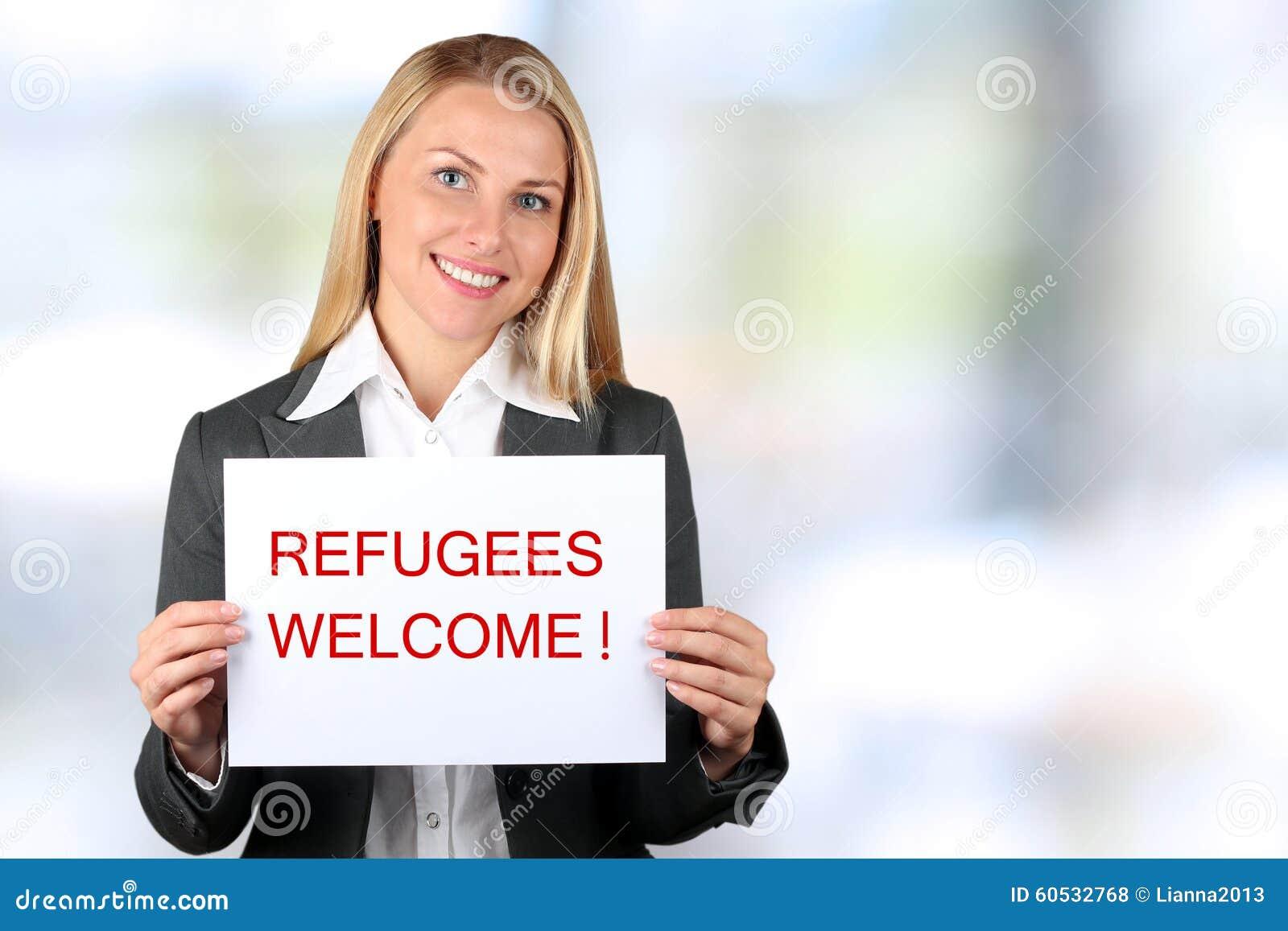 La mujer sonriente que sostiene una bandera blanca con palabras acoge con satisfacción a refugiados