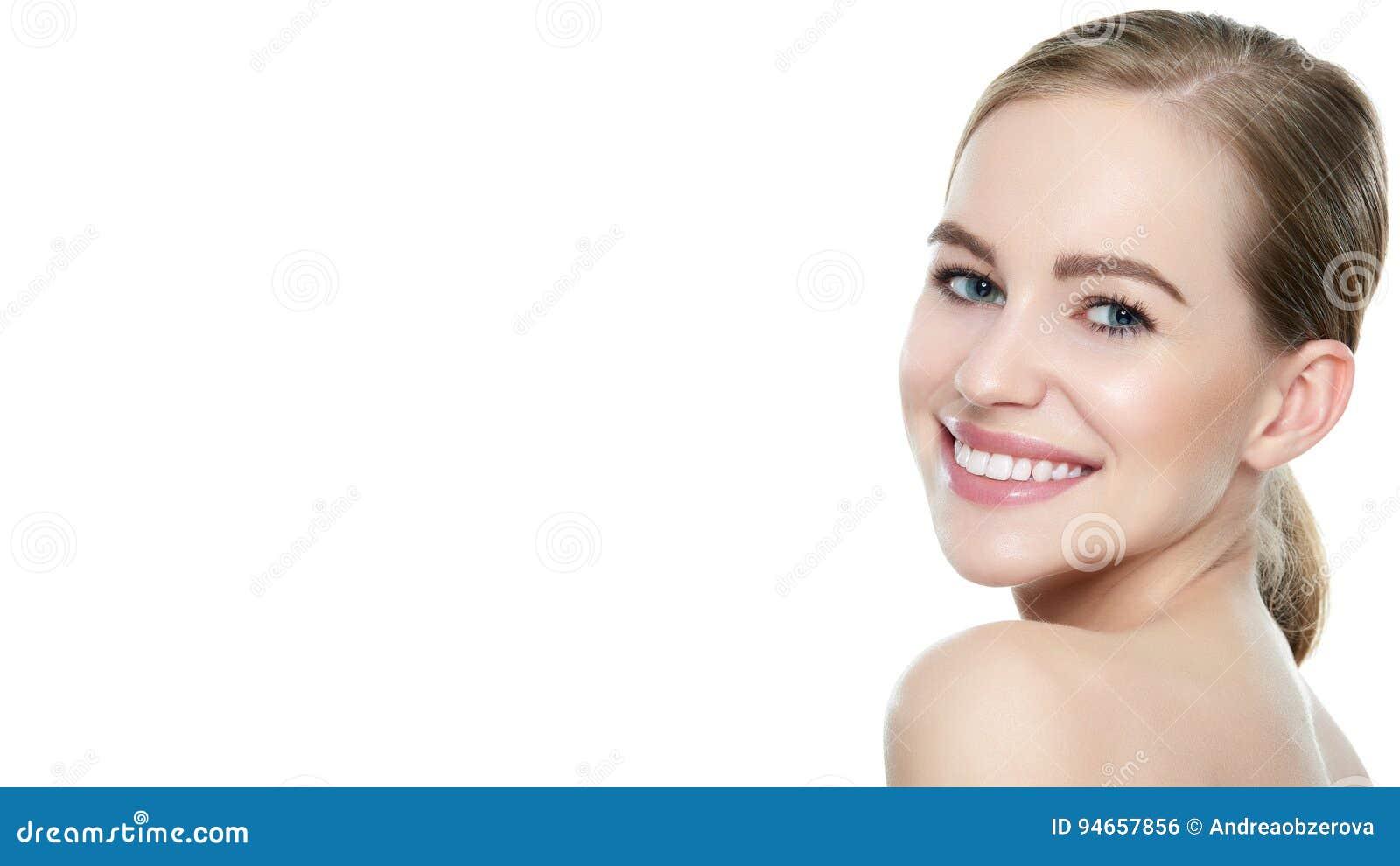 La mujer sonriente rubia joven hermosa con la piel limpia, el maquillaje natural y perfeccionan los dientes blancos