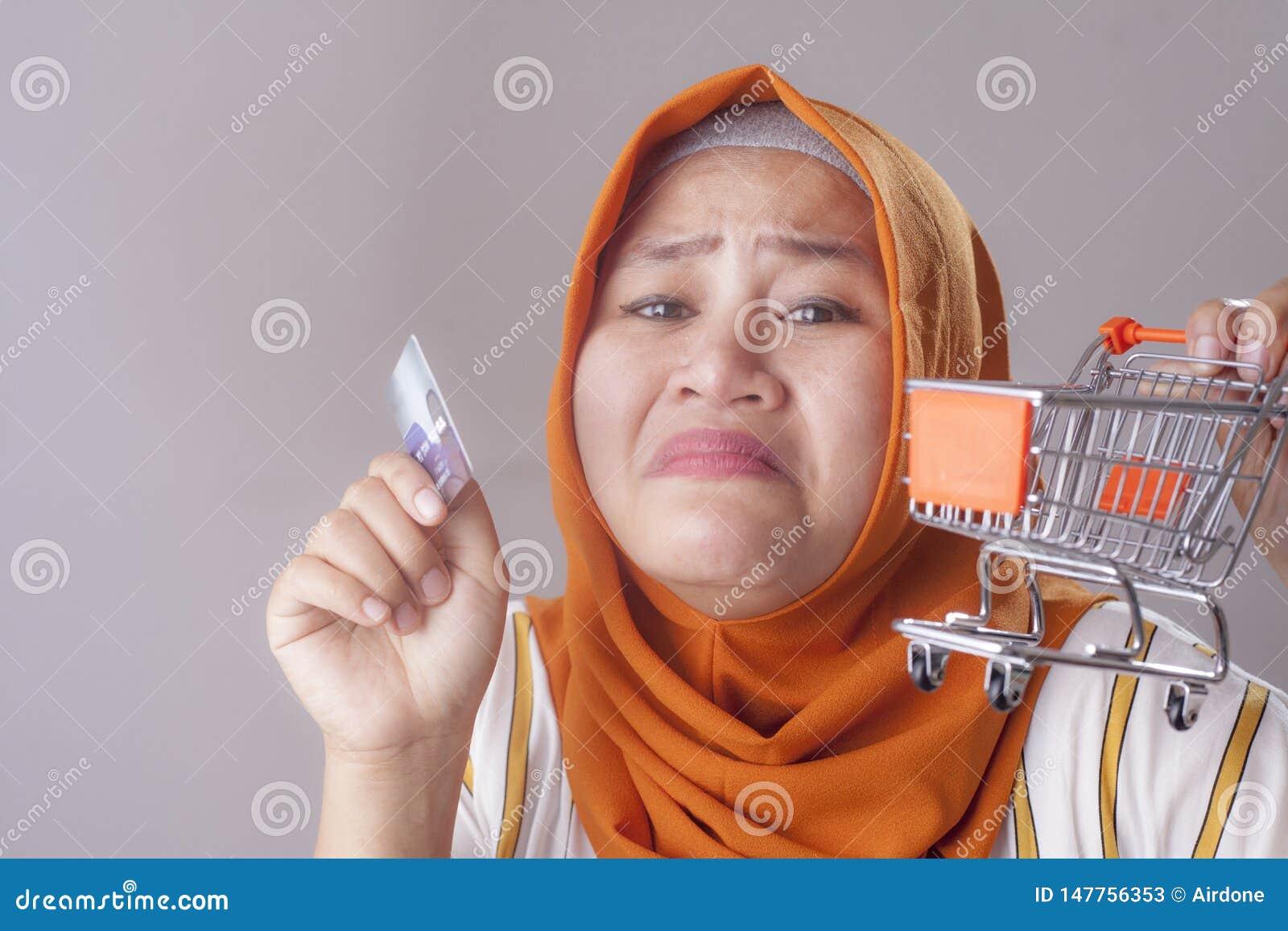 La mujer triste sostiene la tarjeta de cr?dito, concepto de la quiebra