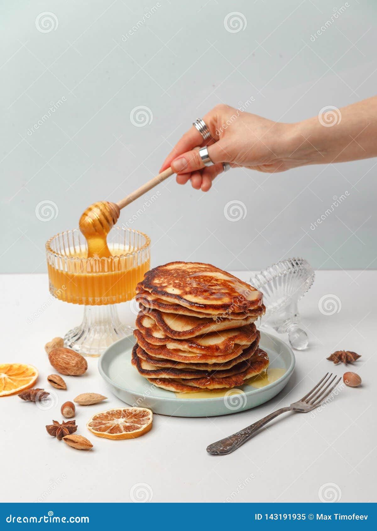La mujer vierte la miel en las crepes El concepto de un desayuno delicioso