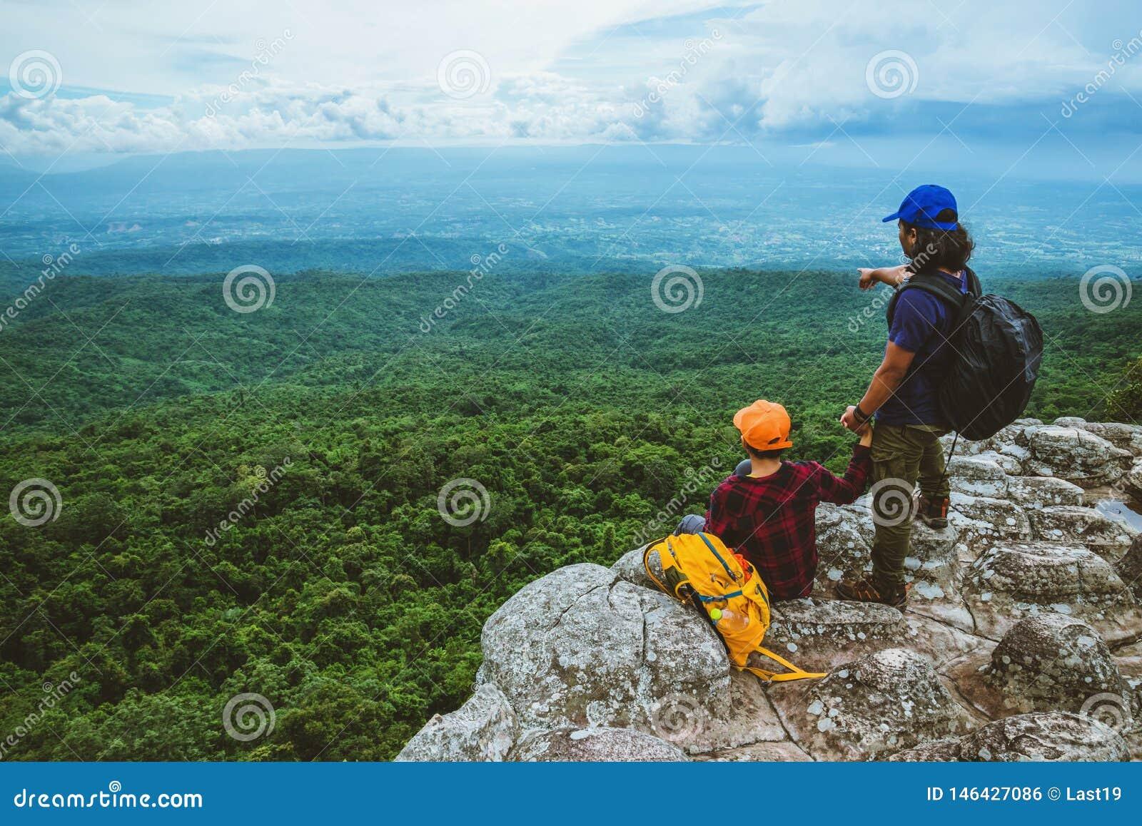 La mujer y los hombres del amante que viajan los asiáticos se relajan en el día de fiesta El mapa de la visión explora las montañ