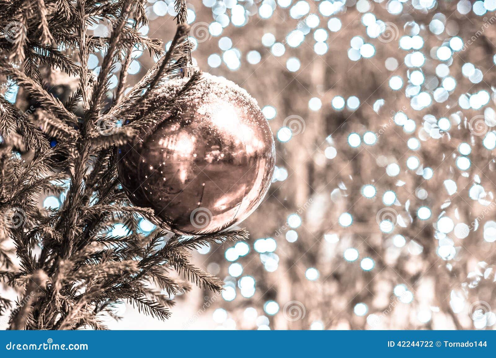 La neige a couvert la boule de décoration sur un arbre de Noël desaturated
