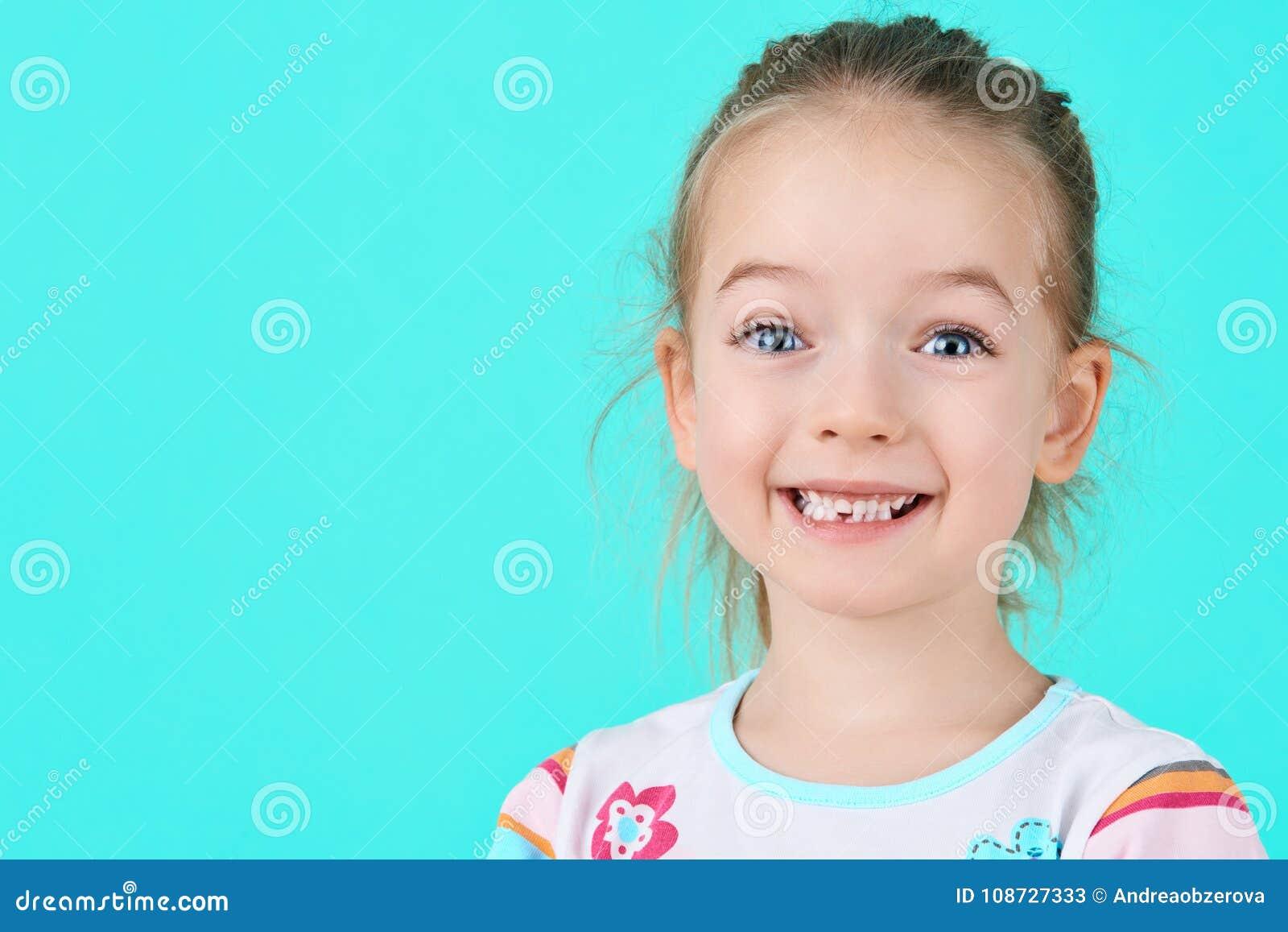 La niña adorable que sonreía y que mostraba apagado su primera perdió el diente de leche Retrato lindo del preescolar