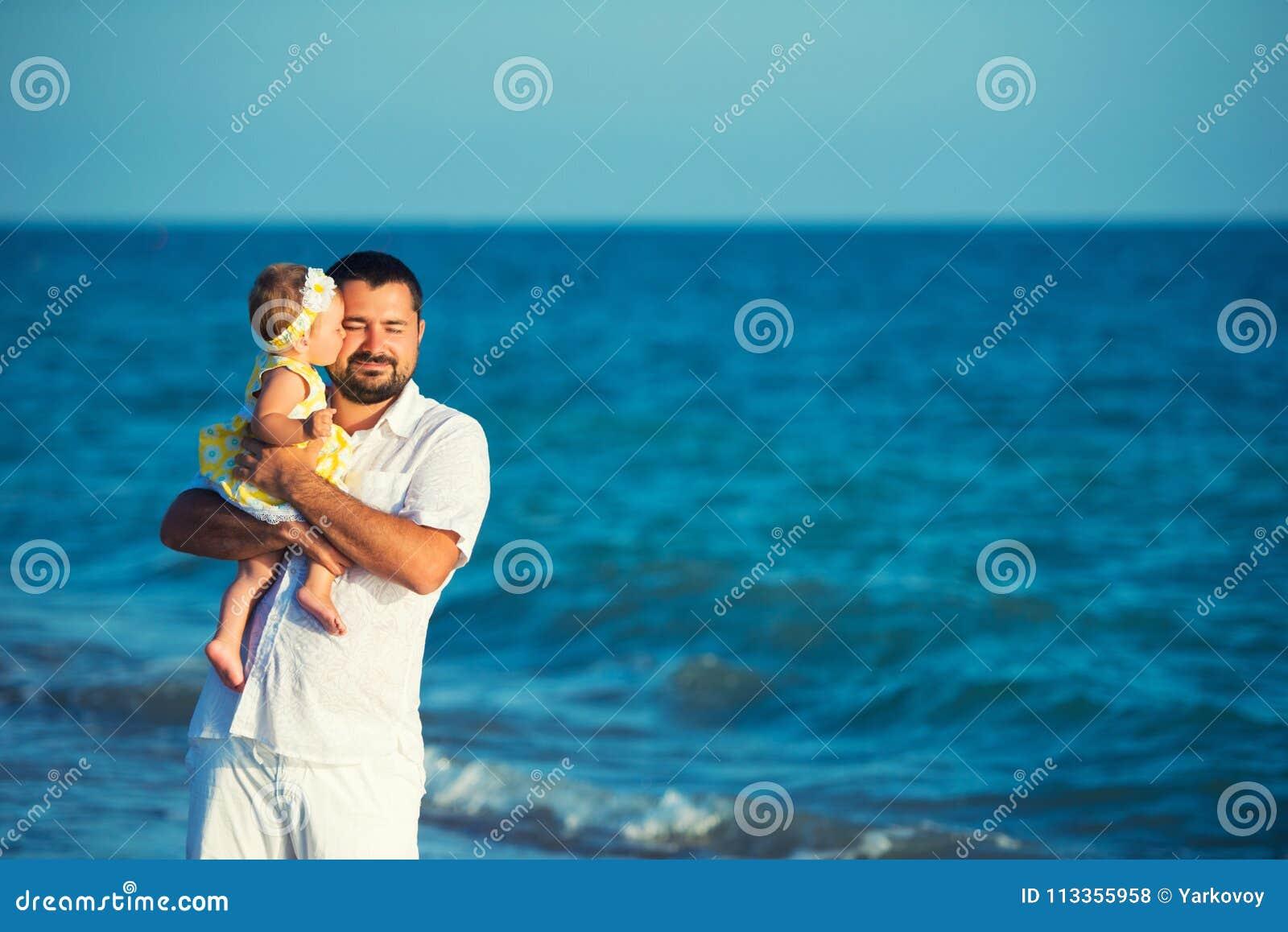 La niña besa a su papá Padre feliz que juega con la pequeña hija linda en la playa