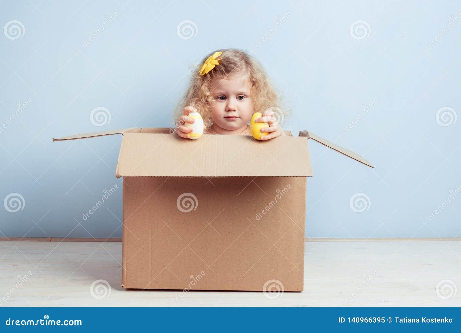 La niña bonita con la flor amarilla en su pelo y teñió los huevos en sus manos se sienta en la caja de cartón en el fondo