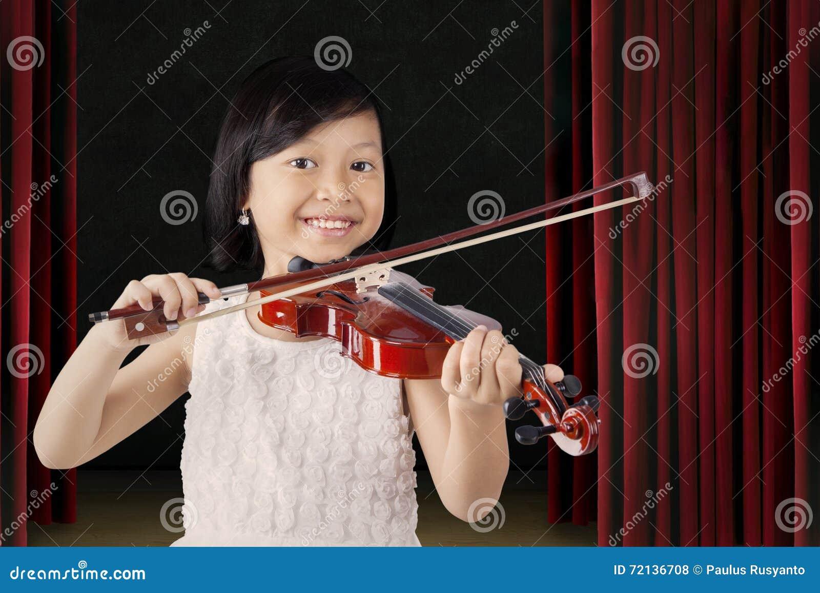 La niña bonita toca el violín en la etapa