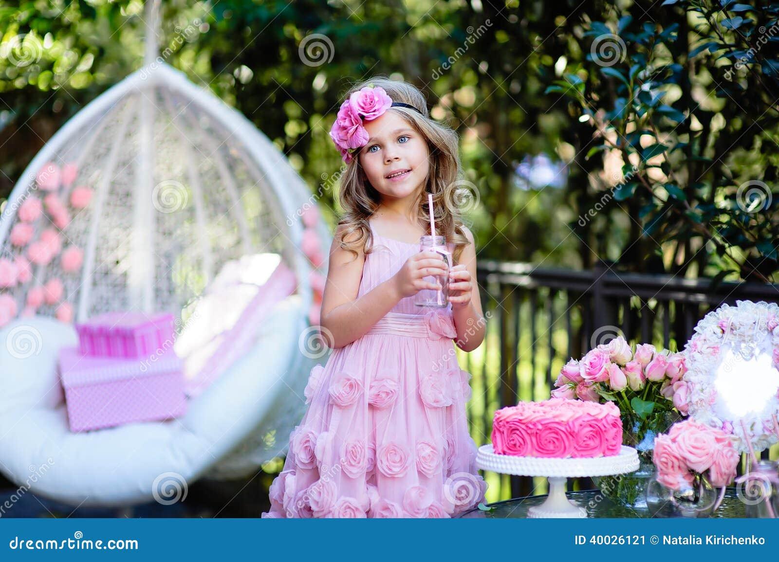 La niña celebra el partido del feliz cumpleaños con la rosa al aire libre