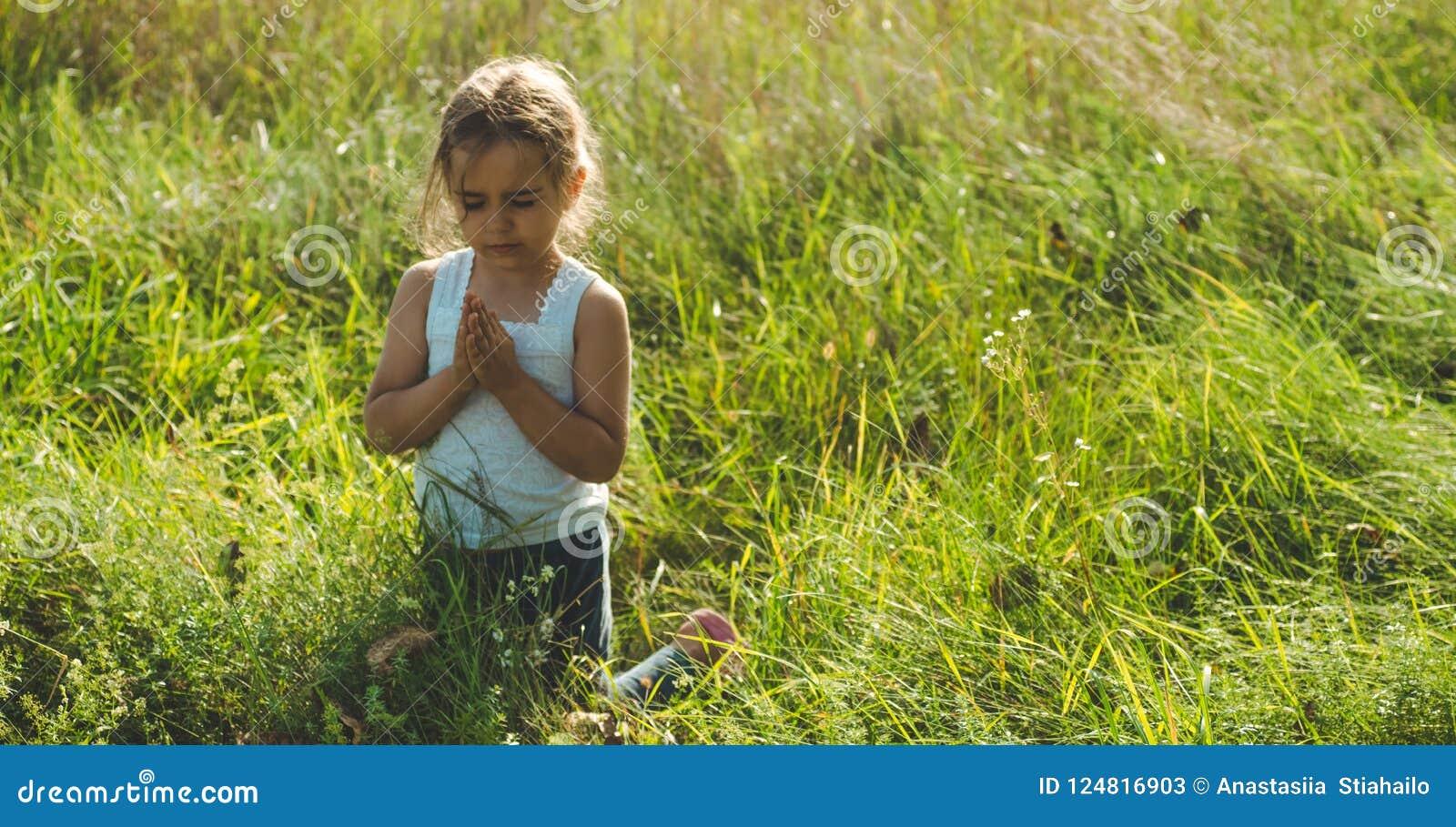 La niña la cerró los ojos que rogaba en la puesta del sol Las manos doblaron en el concepto del rezo para la fe, la espiritualida