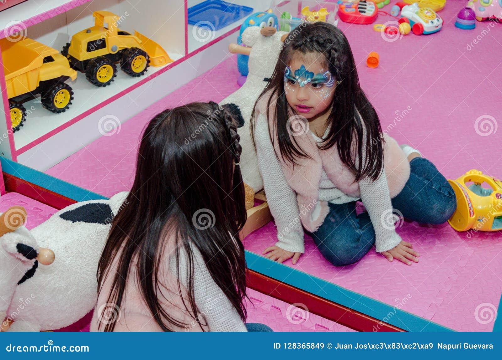 La niña con la cara pintada mira en el espejo