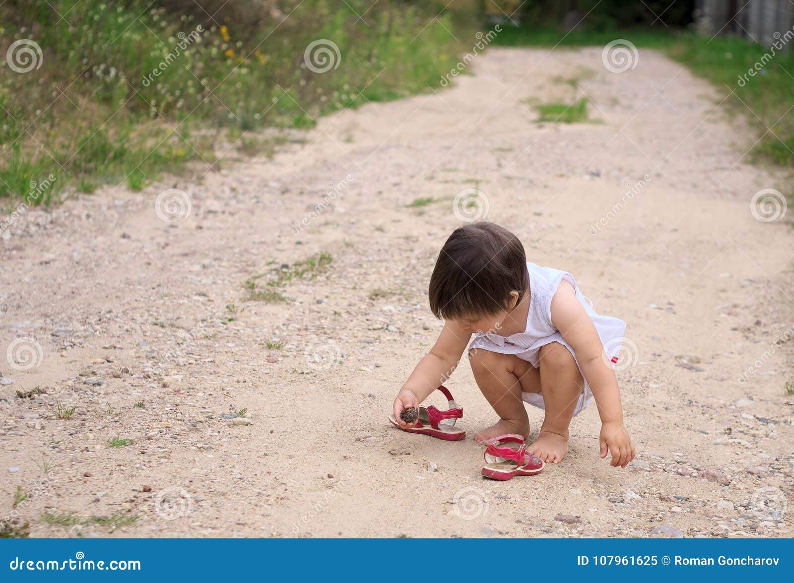 La niña encontró un cono del pino en el camino