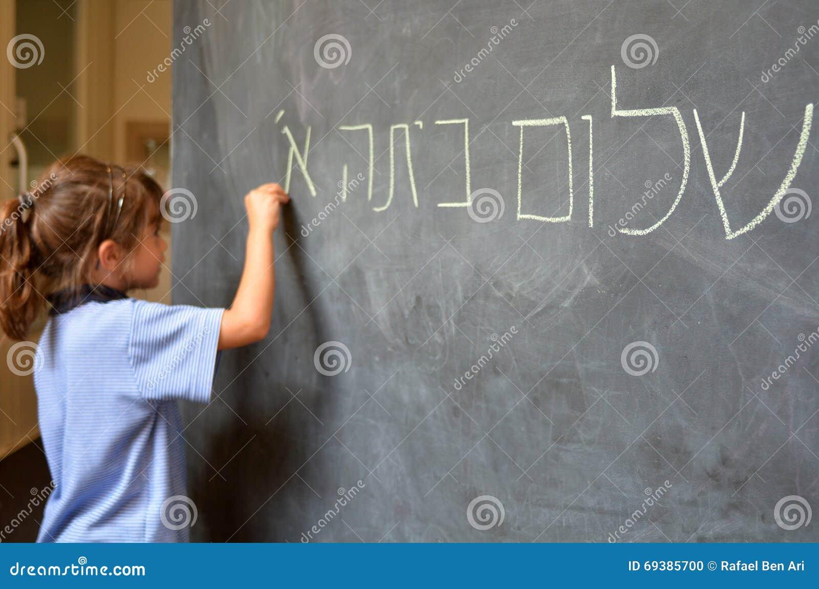 La niña escribe hola saludos del primer grado en hebreo