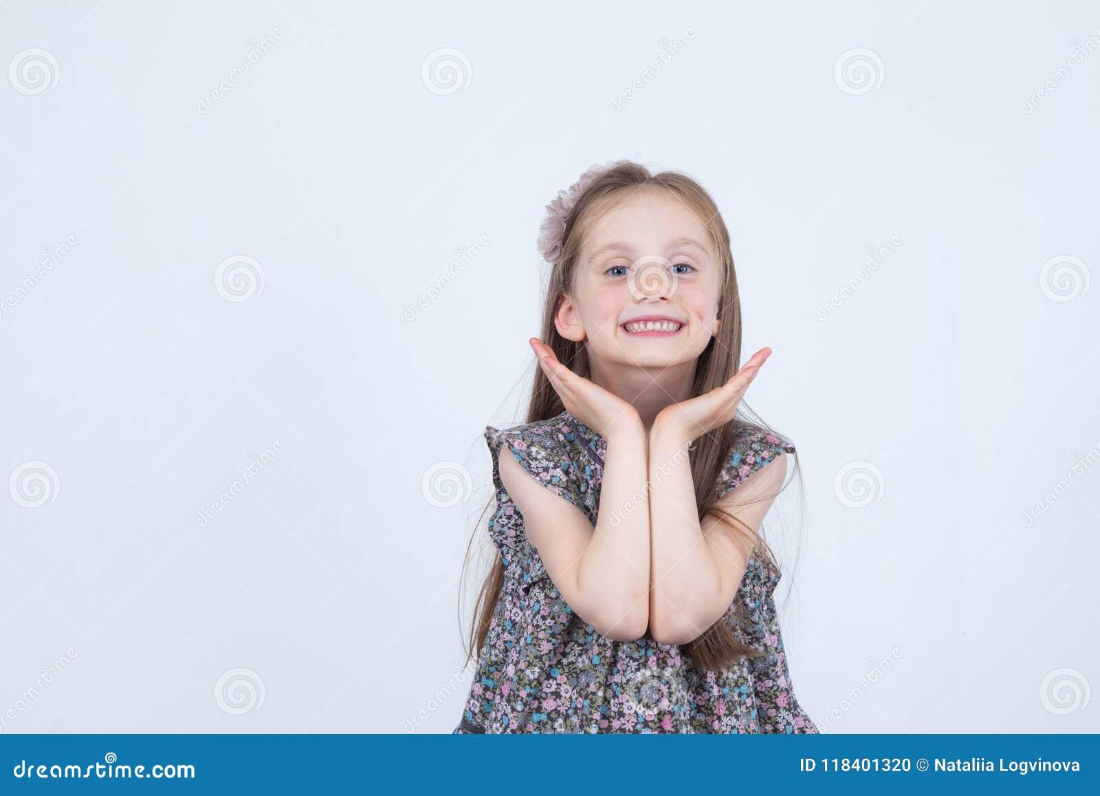 La niña está haciendo caras Expresiones divertidas y felices Padre y niño que juegan junto Preescolar en vestido en el fondo blan