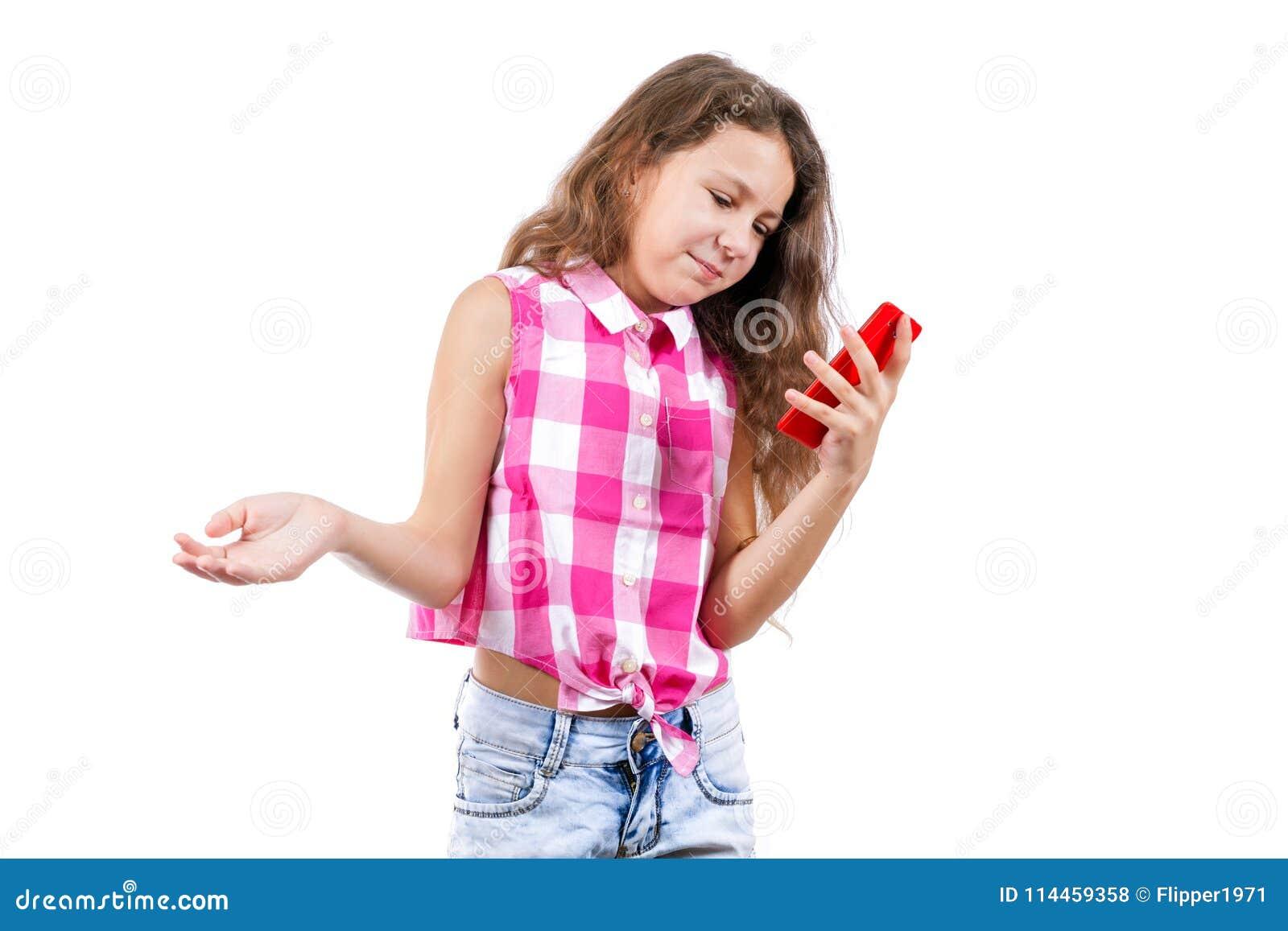 La niña está leyendo SMS en el teléfono y está sonriendo
