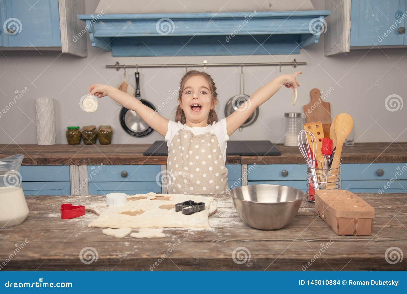 La niña feliz en la cocina está haciendo diversas formas de galletas fuera de la pasta, ayudando a su mamá Peque