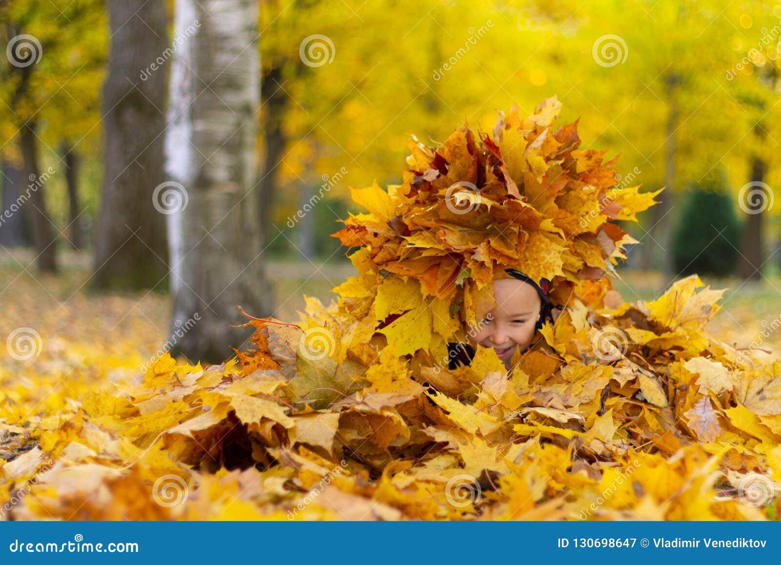 La niña feliz juega con las hojas de otoño en el parque