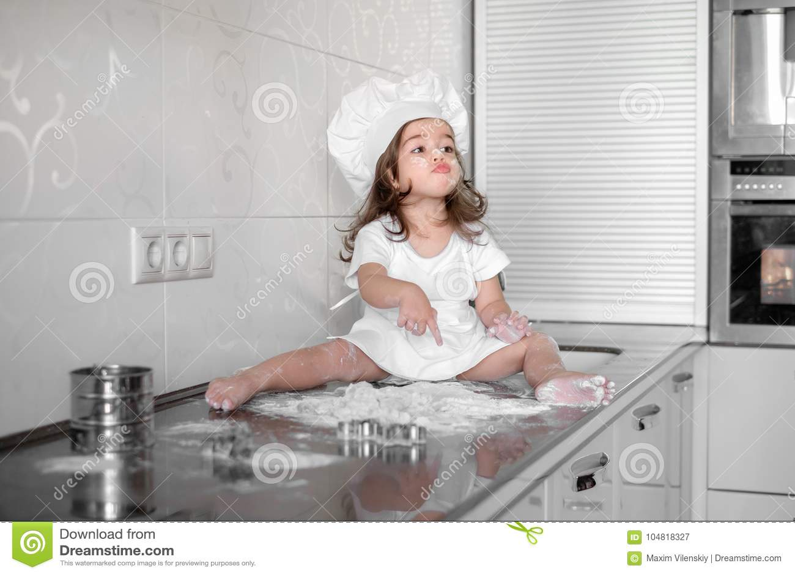 La niña hace la pasta en cocina con el rodillo
