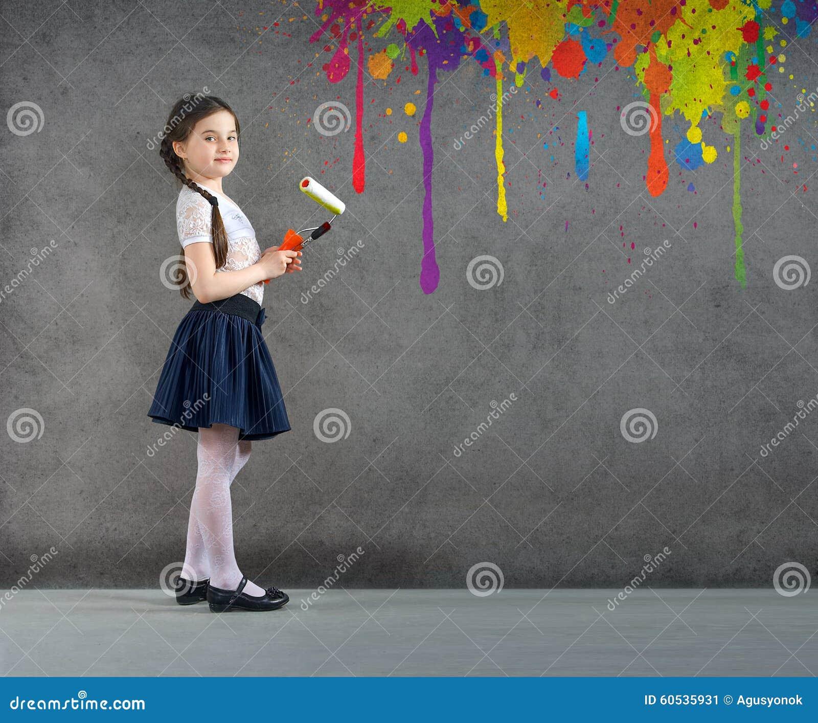 La niña joven sonriente alegre el niño dibuja en las pinturas coloreadas pared del fondo reparar creativos
