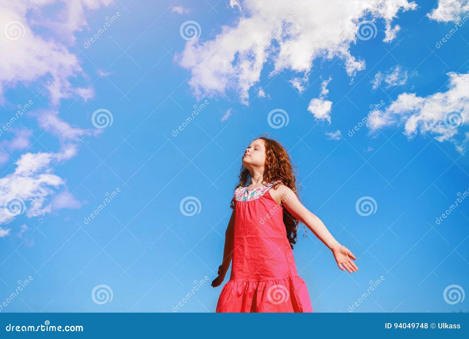 La niña la cerró los ojos y respira el aire fresco