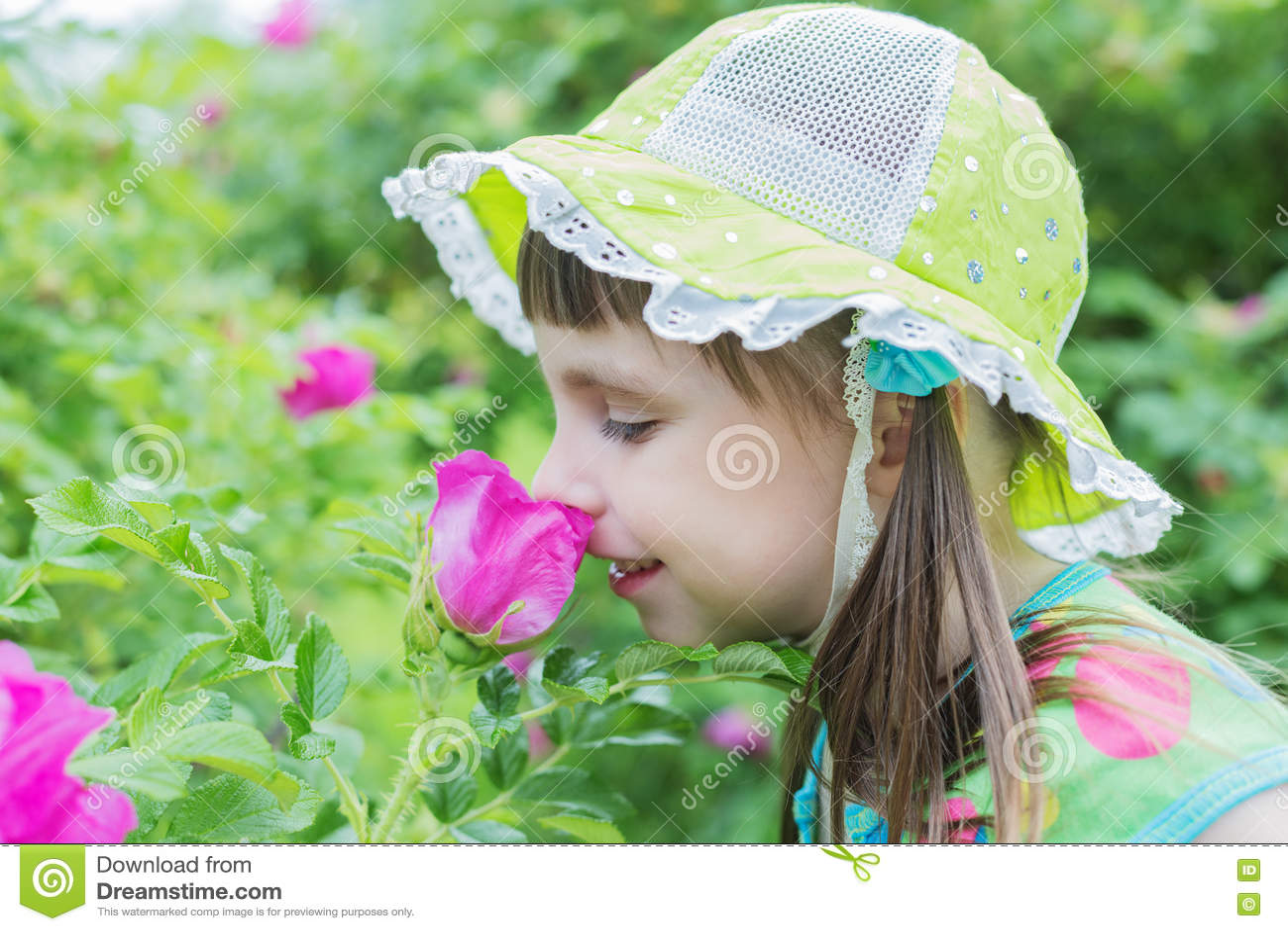 La niña linda inhala el aroma de la flor