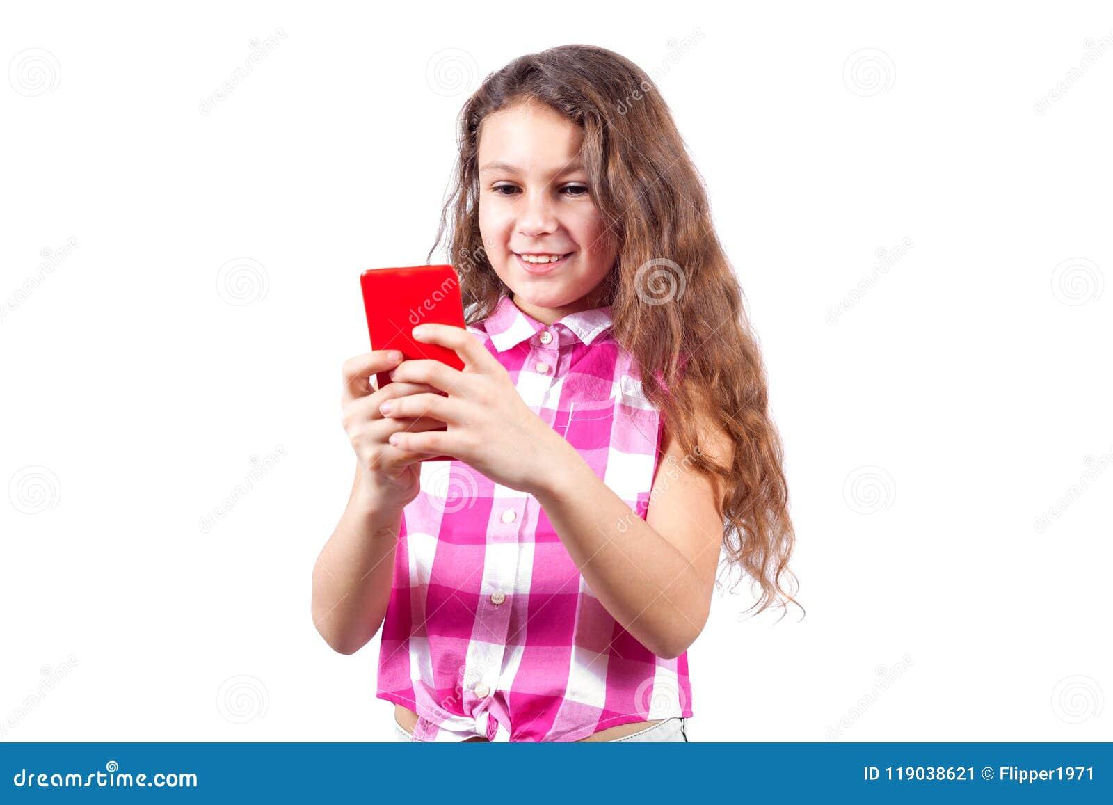 La niña linda mira en smartphone y la sonrisa