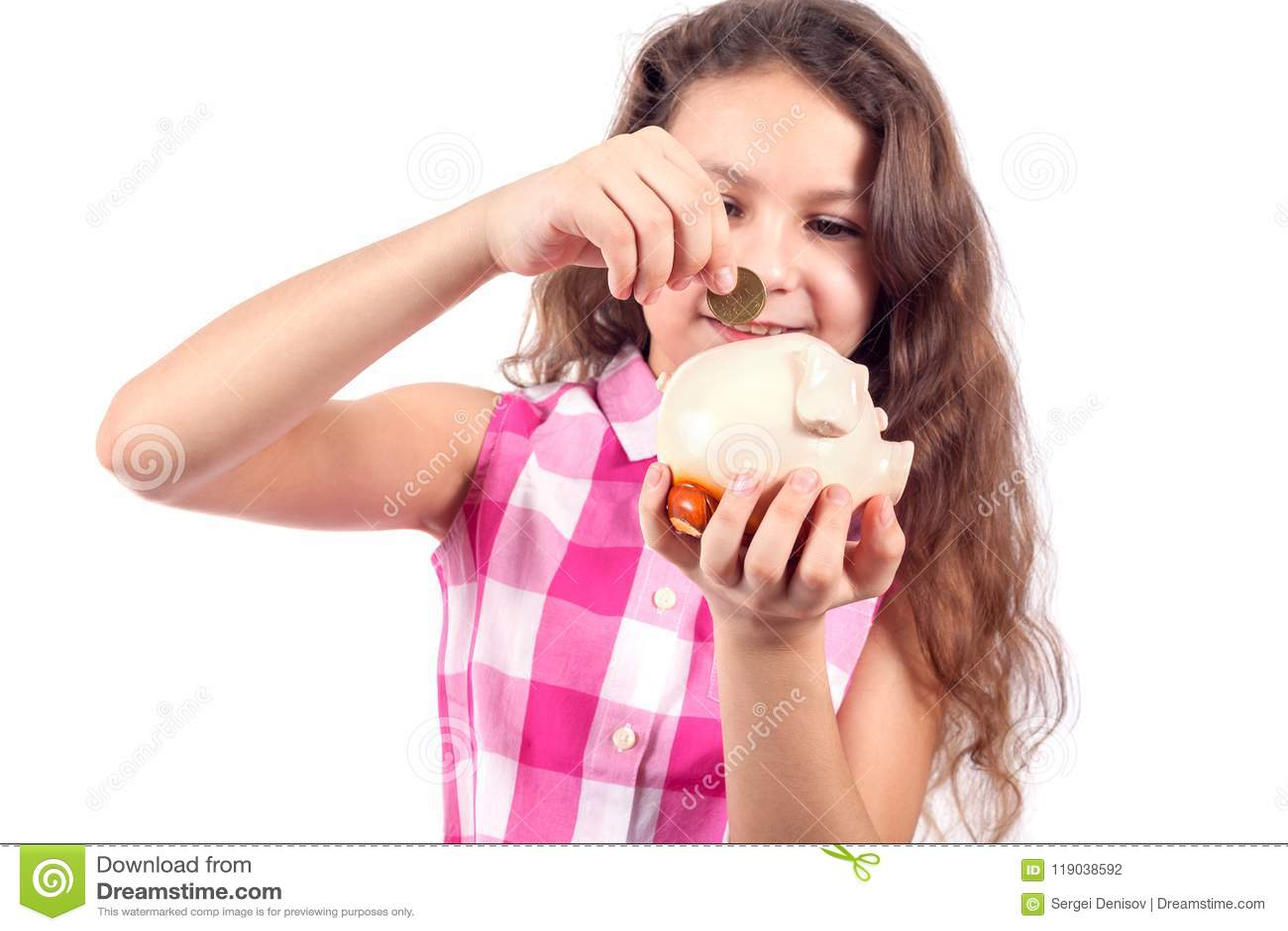 La niña linda pone una moneda en un banco cerdo-guarro